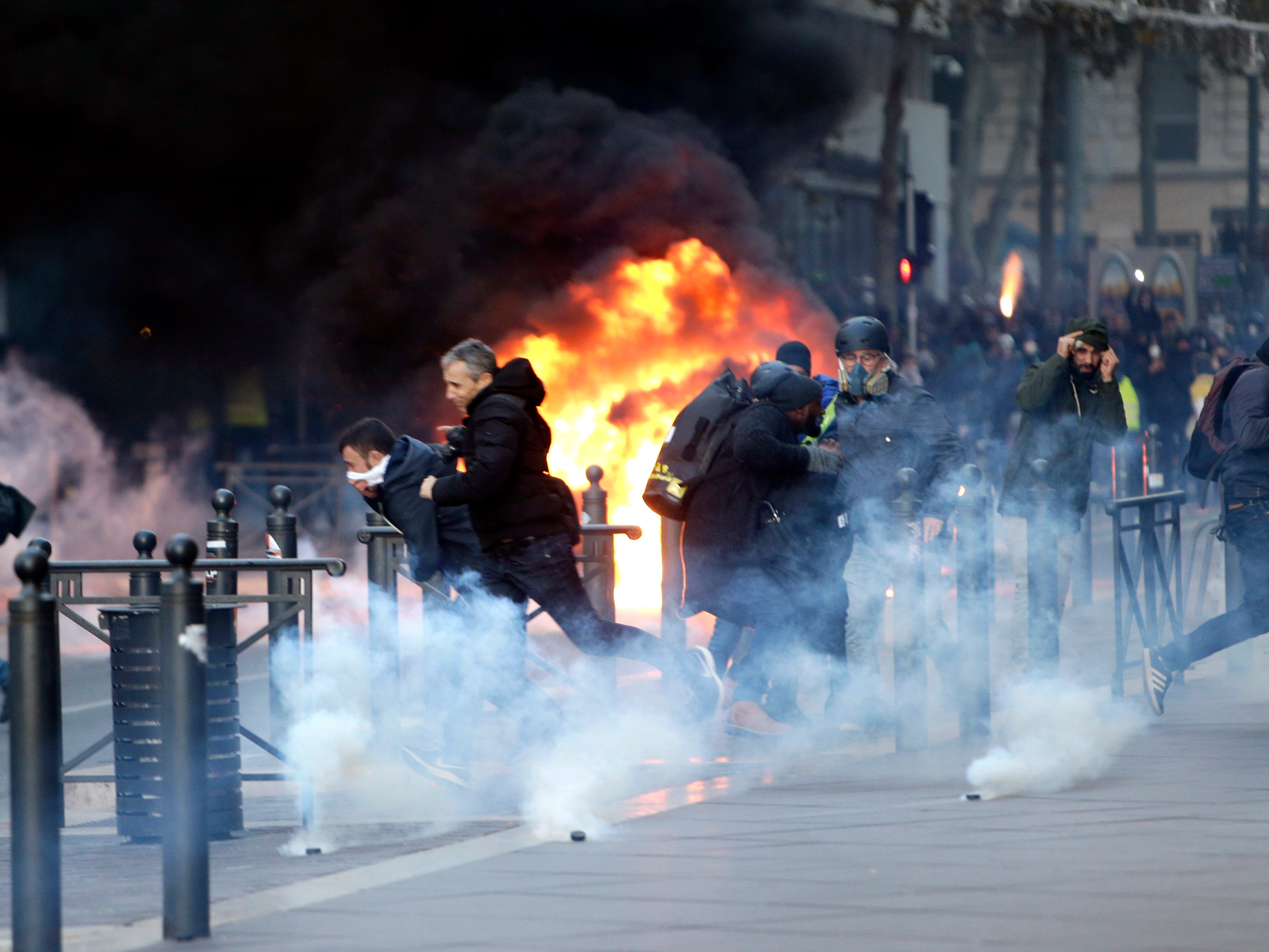 People run away from a burning car during clashes, Saturday, Dec. 8, 2018, in Marseille, southern France. The grassroots movement began as resistance against a rise in taxes for diesel and gasoline, but quickly expanded to encompass frustration at stagnant incomes and the growing cost of living.