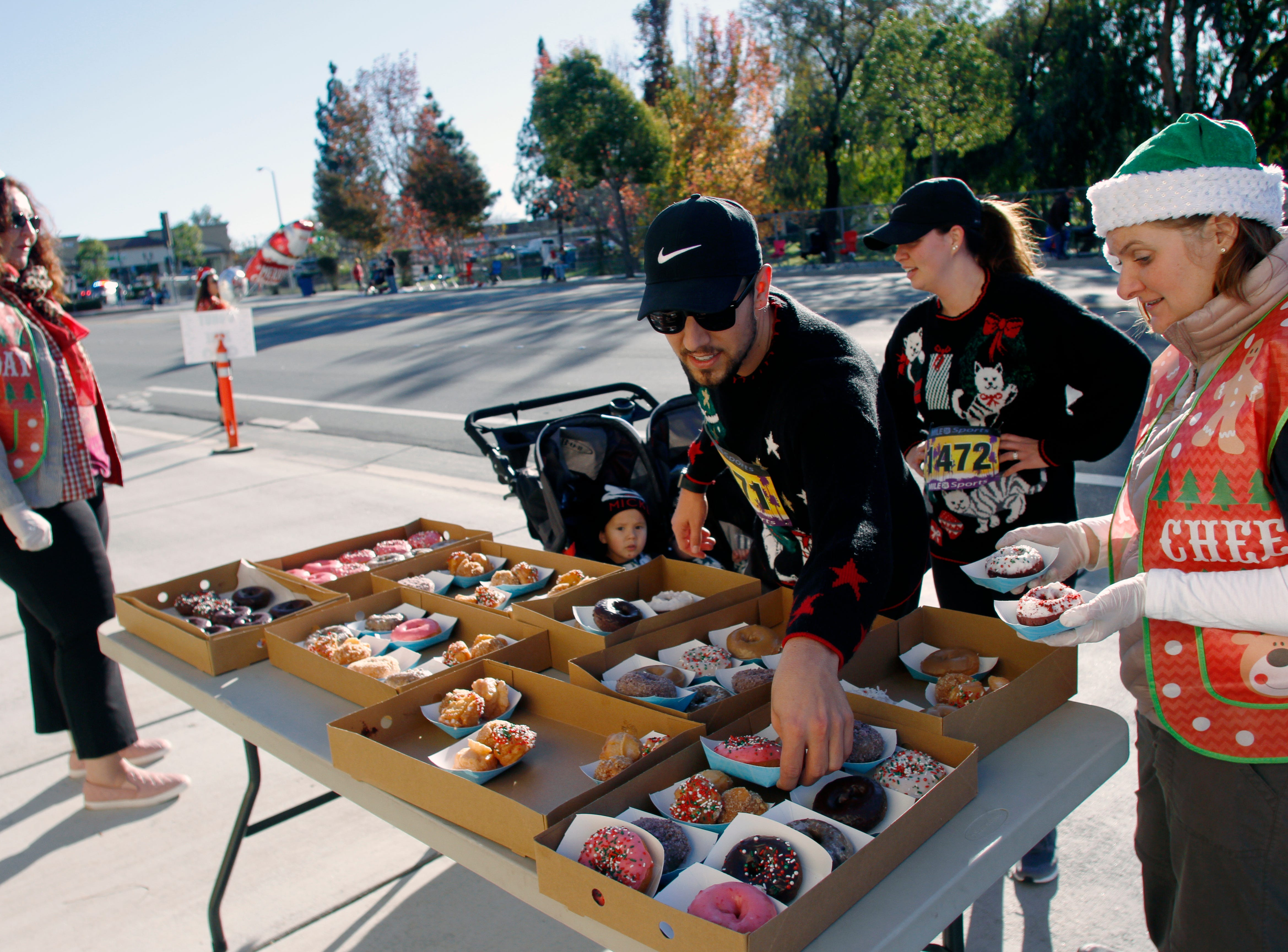 Run participants Josh and Lexi Warren grab doughnuts at an aid station near Rolling Pin Donuts as volunteer Heather Roberts hands out the treats on Saturday during Christmas festivities in Camarillo that included a parade and more.