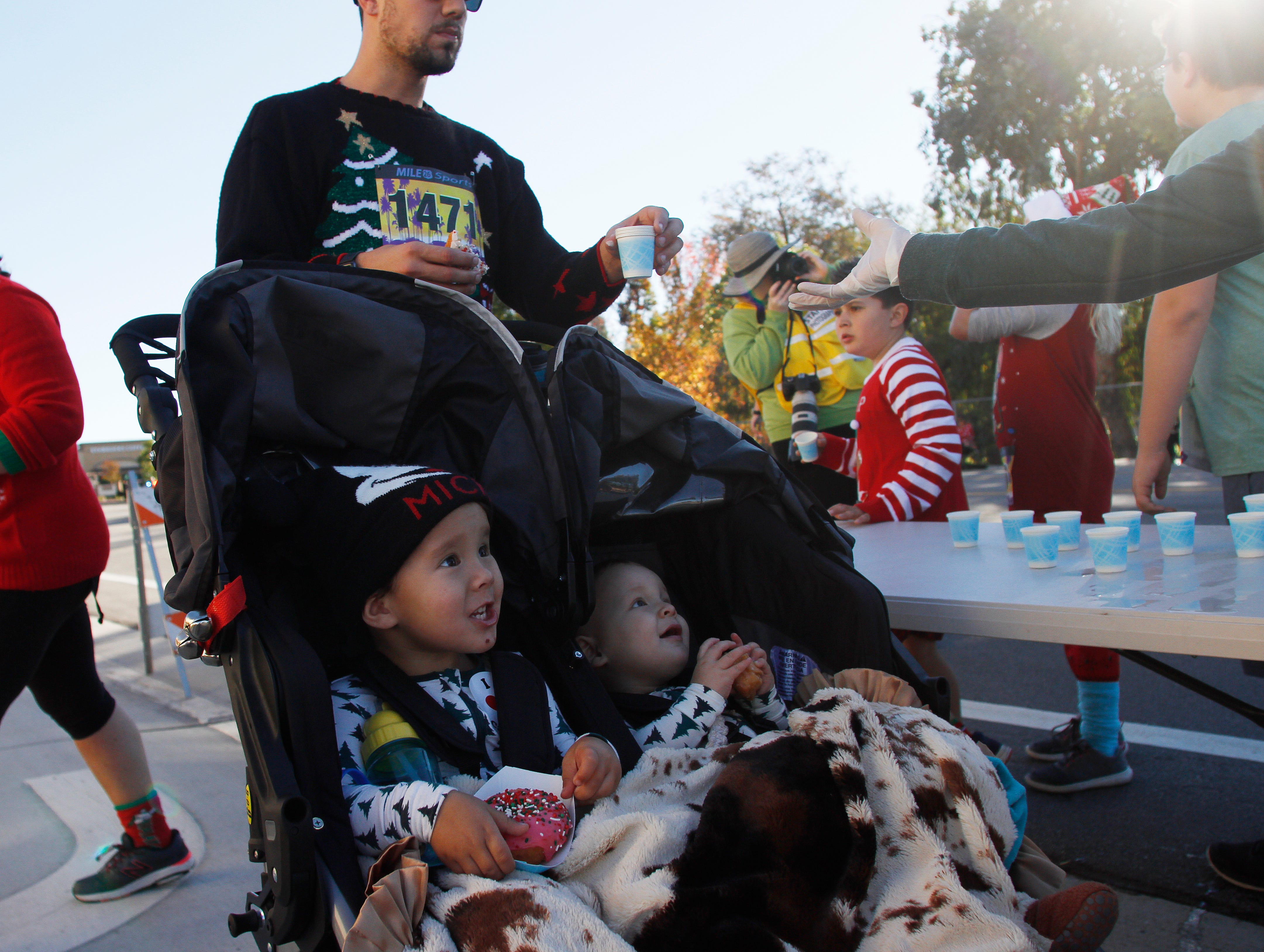 From left in front, Cove and Kai Warren eat doughnuts as their dad, Josh Warren, receives water at an aid station during the 5K run that was part of Christmas festivities Saturday in Camarillo.