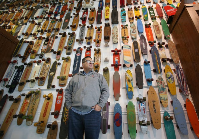 Skateboarding Hall of Fame Founder Todd Huber stands in front of wall that is dedicated to skateboards of all types at at his new location inside the Simi Valley Town Center.