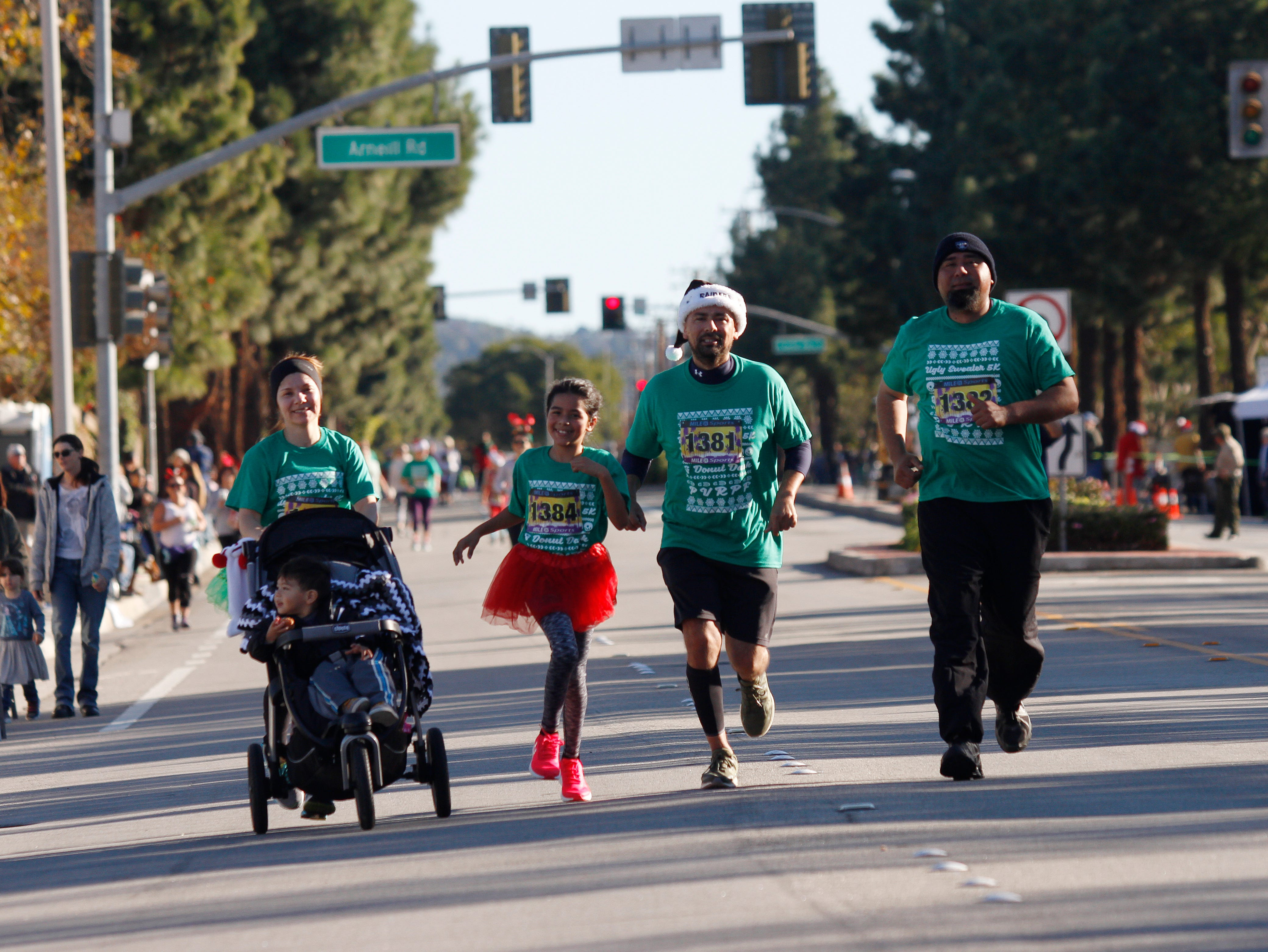 From left, Irma Andrade, pushing her son Ebe Jr., runs next to her daughter Layah, husband Ebe and brother-in-law Fernando on Saturday during Christmas festivities in Camarillo that included a run, parade and more.