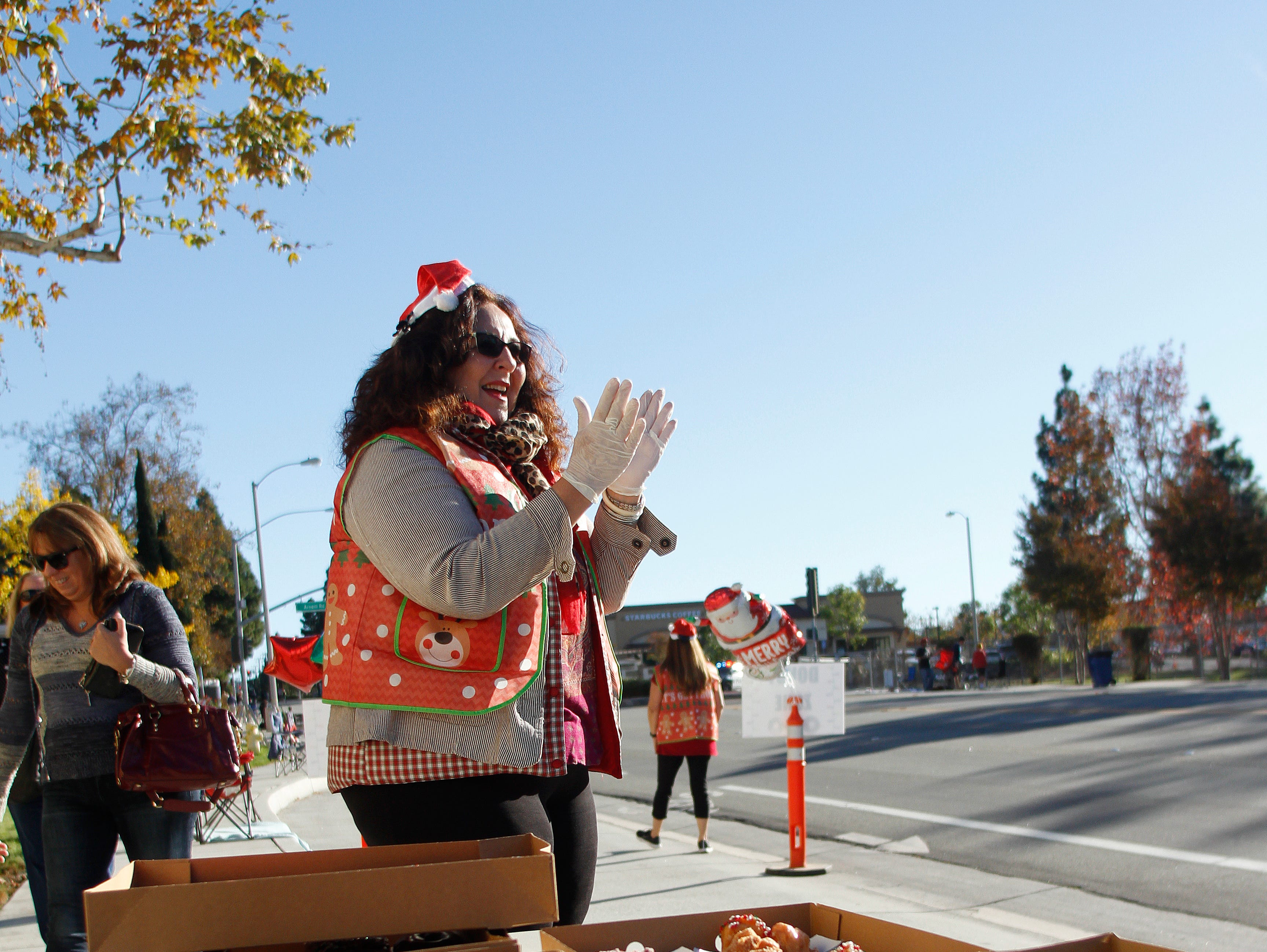 Volunteer Linda Lamb cheers for 5K participants as she stands ready to hand out doughnuts and water at an aid station during Christmas festivities in Camarillo that also included a parade.