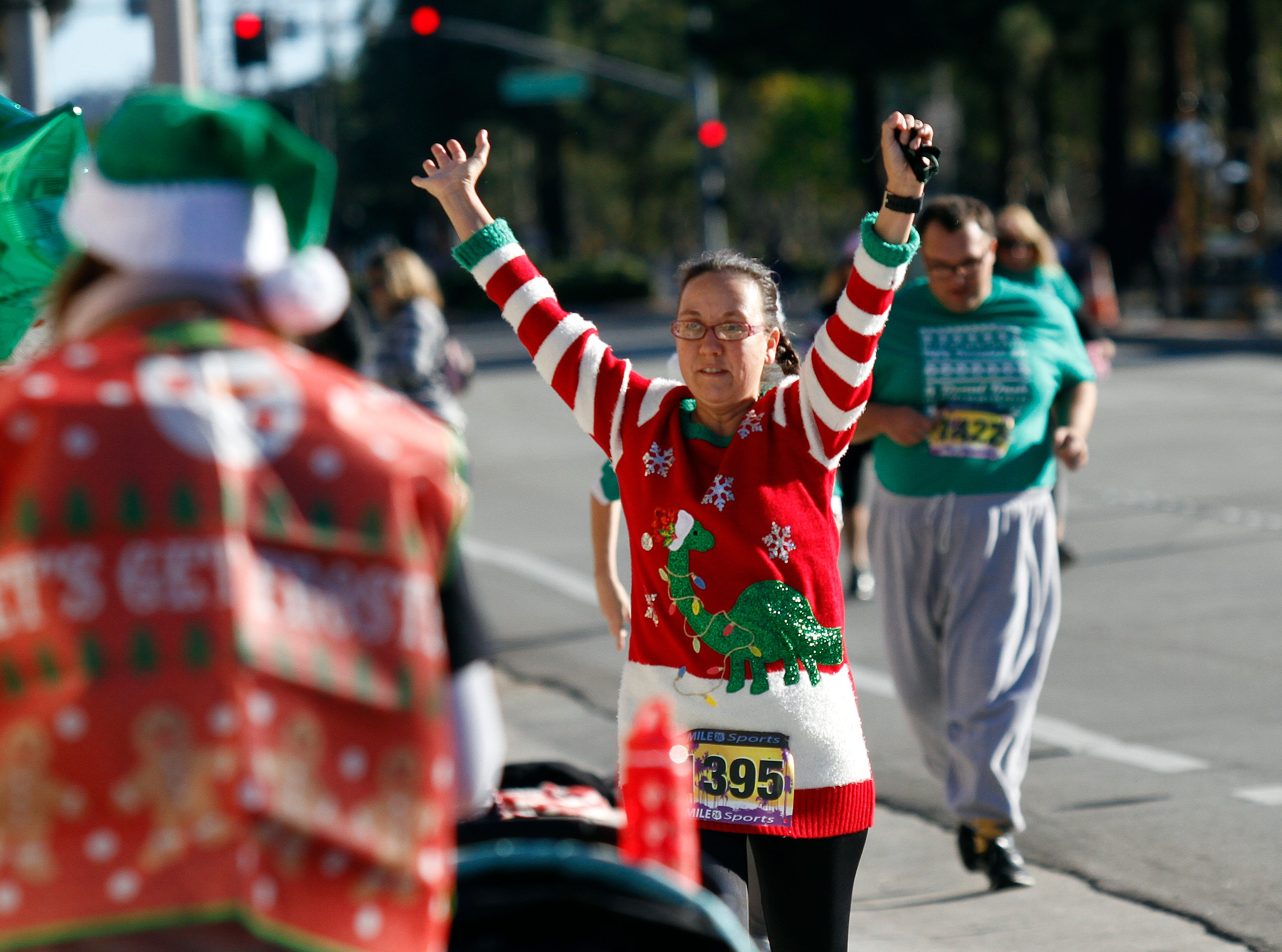 Corey Branchflower, a running coach for a special needs group called Team in His Image from the Oxnard Calvary Chapel, celebrates with her team at the end of their run Saturday during Christmas festivities in Camarillo.