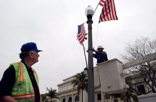 Ventura City Council member Jim Monahan watches John Contreras hang flags at City Hall in this file photo.