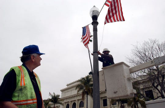 Ventura City Council member Jim Monahan watches John Contreras hang flags at City Hall in this file photo.