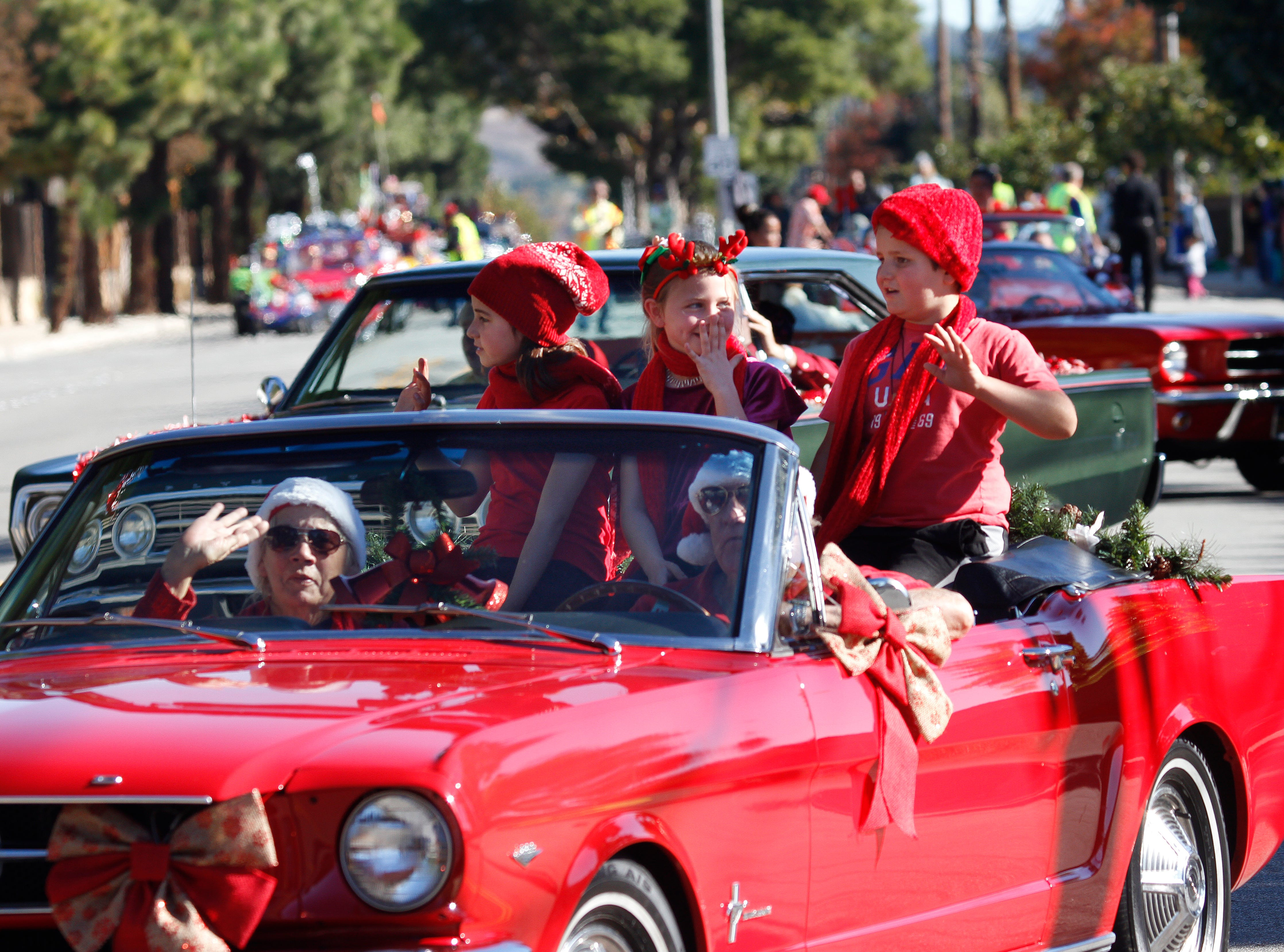 From left in back, Samantha Lambert, Taylor Hone and Jack Lambert wave to the crowd during Saturday's Christmas parade in Camarillo.
