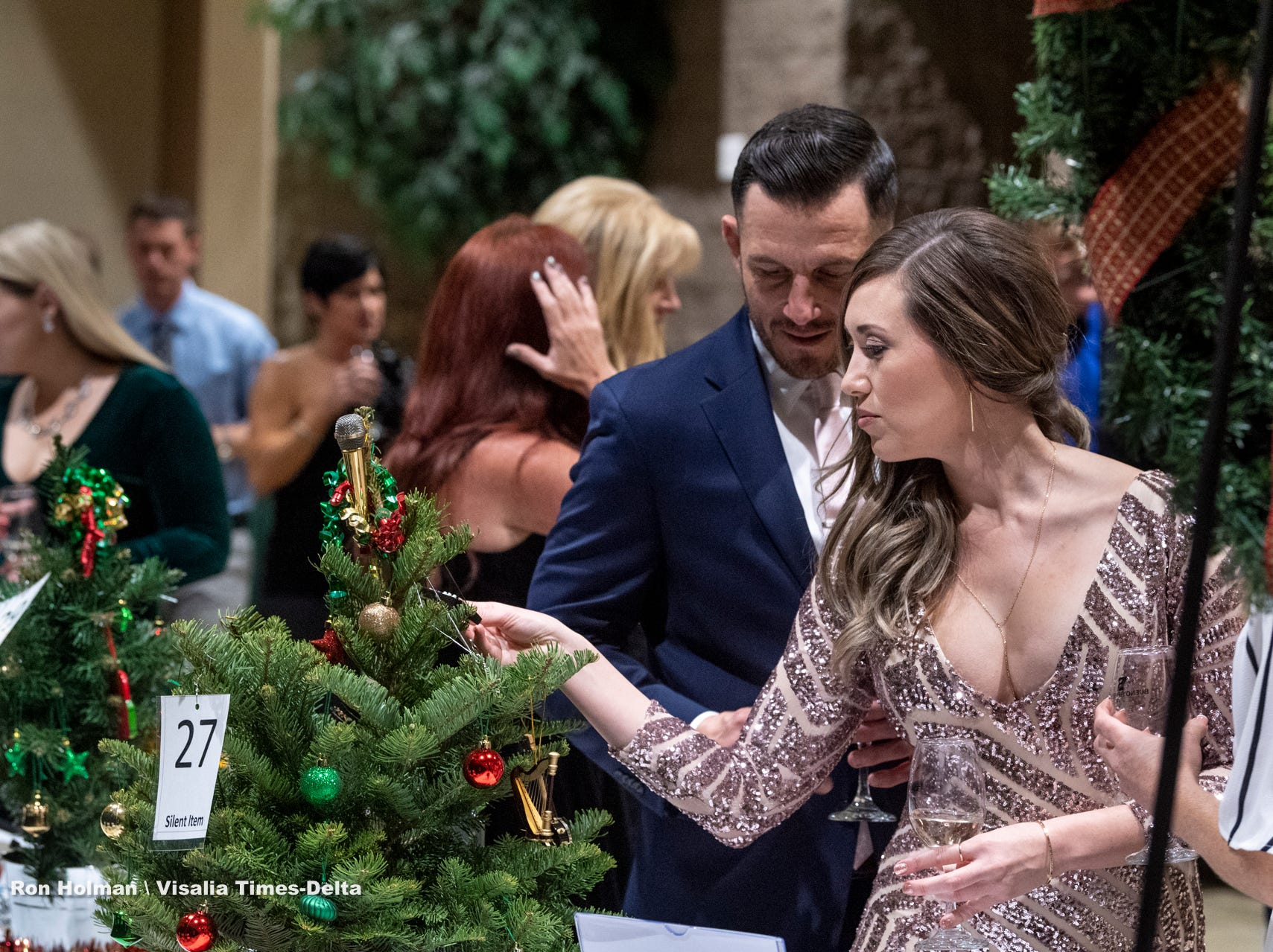 "Sabrina Quair, right, and Cody Adamo browse silent auction items during Visalia's 38th Annual Christmas Tree Auction on Friday, December 7, 2018. This year's theme was ""A Holiday Affair."" The live auctions alone generated nearly $60,000 in bids."