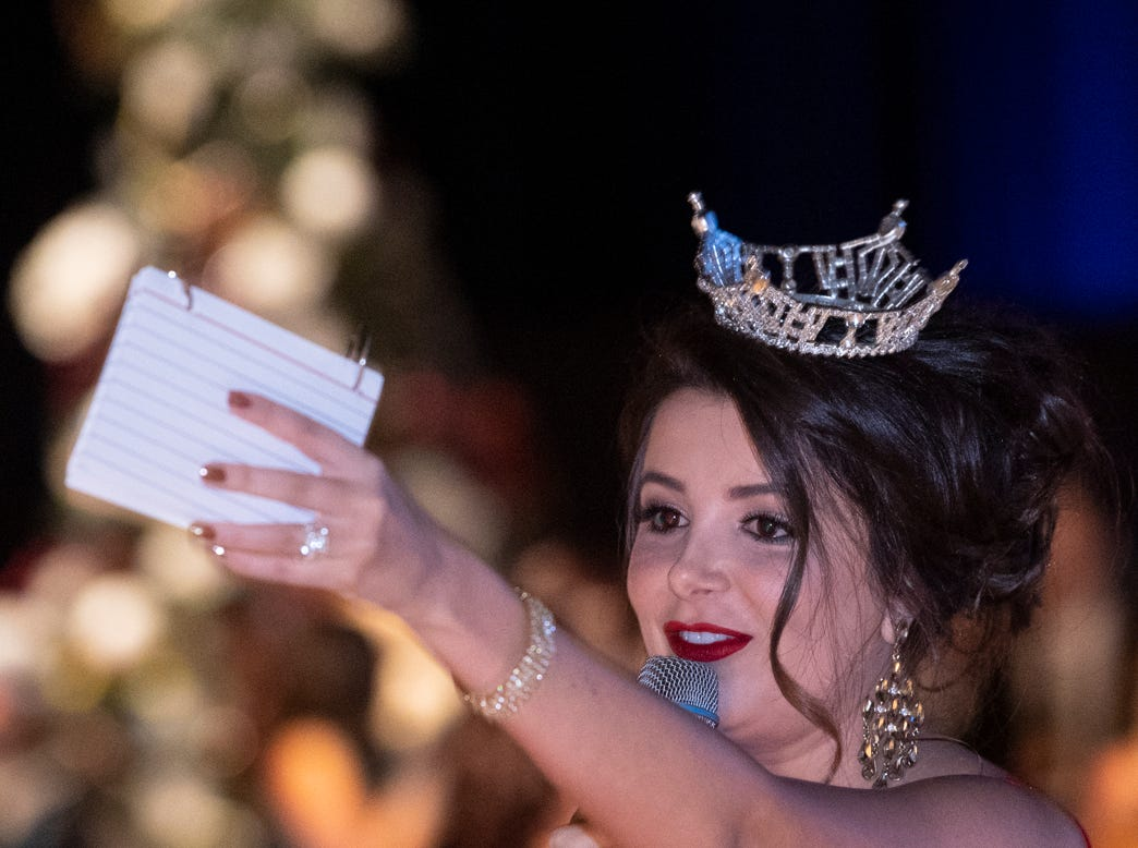 "Miss Central Valley Alexandra Macedo acknowledges a bidder during Visalia's 38th Annual Christmas Tree Auction on Friday, December 7, 2018. This year's theme was ""A Holiday Affair."" The live auctions alone generated nearly $60,000 in bids."