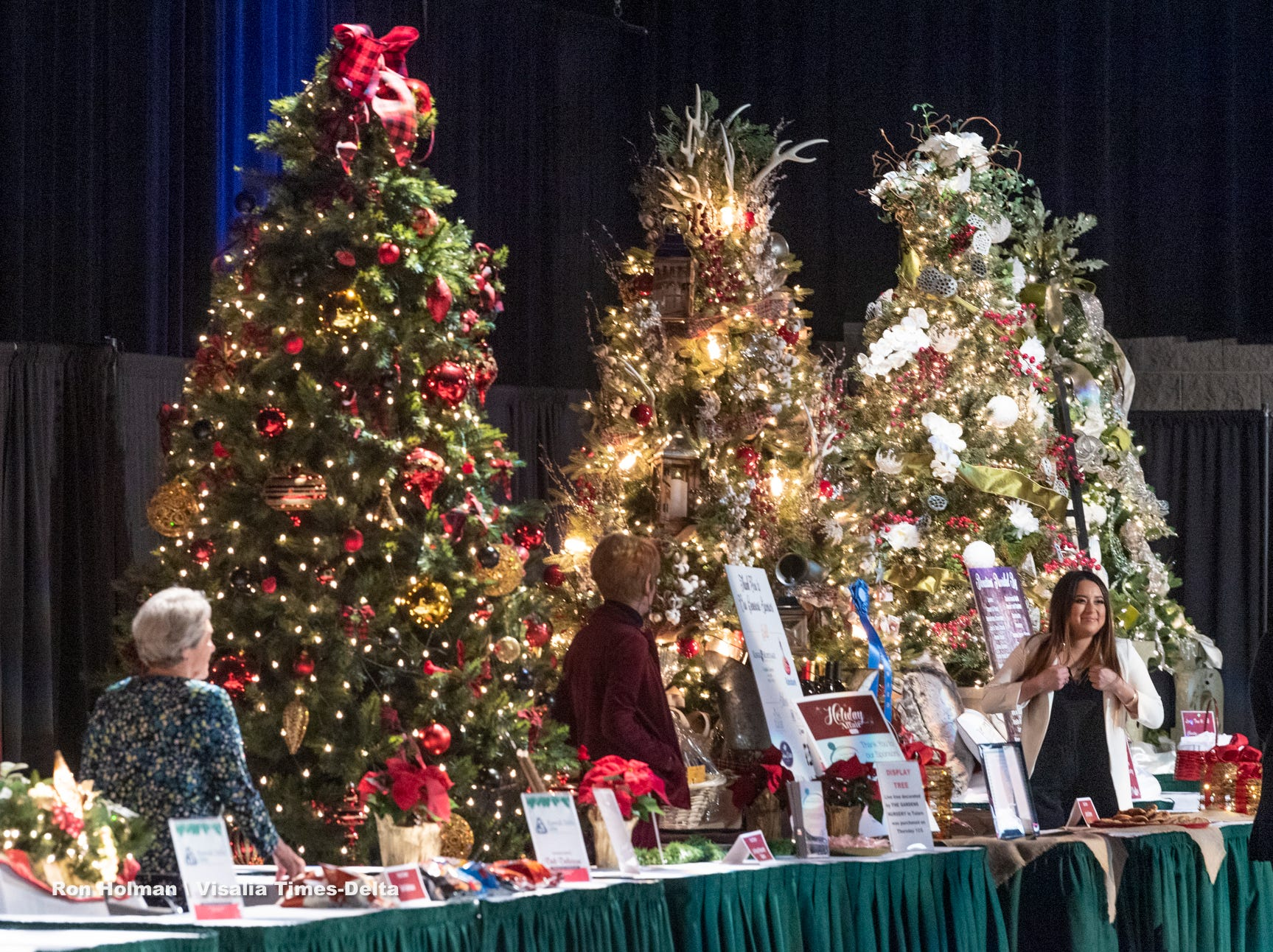 "Visitors browse three of the 14 live auction trees on display during the public preview to Visalia's 38th Annual Christmas Tree Auction on Friday, December 7, 2018. This year's theme is ""A Holiday Affair."""