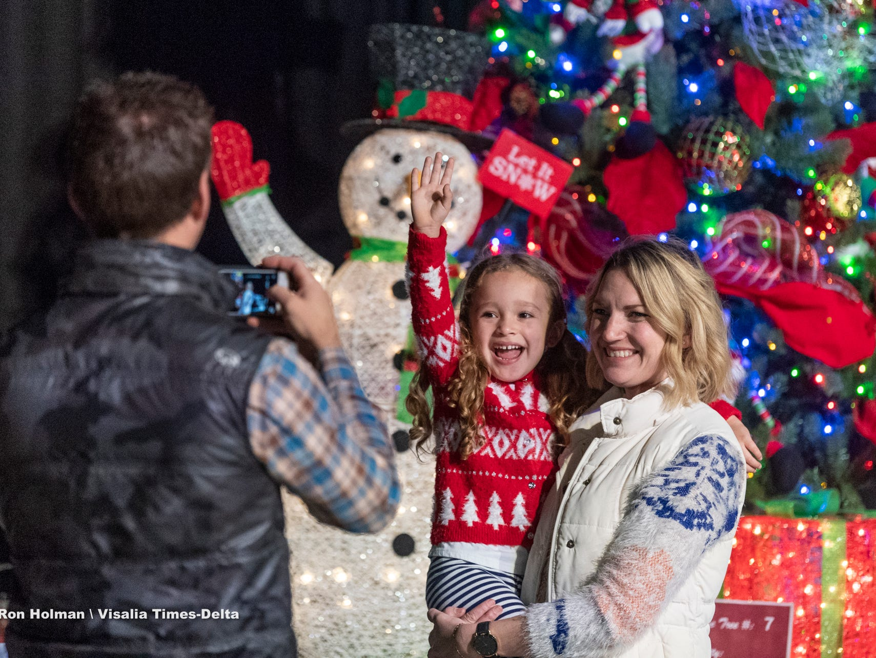 "Candace Feely and her daughter Eden Feely, 3, pose for pictures in front of one of the live auction trees during the public preview to Visalia's 38th Annual Christmas Tree Auction on Friday, December 7, 2018. This year's theme is ""A Holiday Affair."""