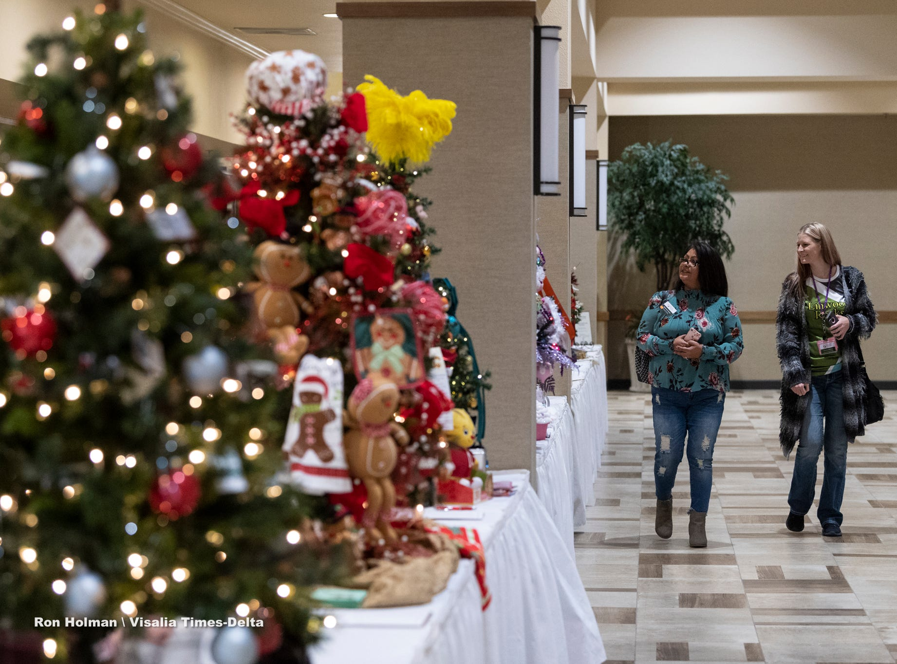 "Shauna Ramos, right, and Stephanie Huerta browse silent auction trees during the public preview to Visalia's 38th Annual Christmas Tree Auction on Friday, December 7, 2018. This year's theme is ""A Holiday Affair."""