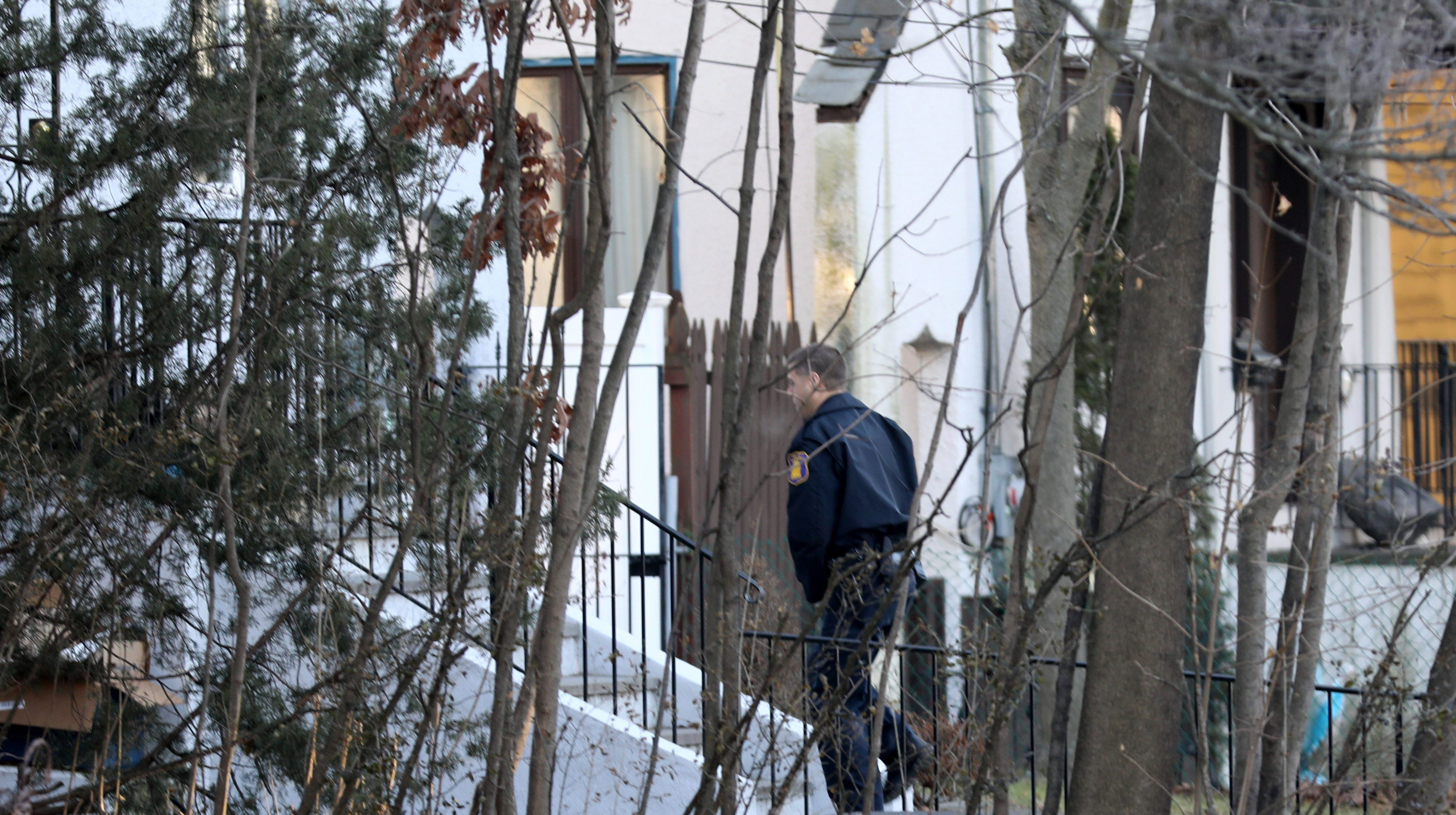 A Yonkers police officer walks toward a house on...