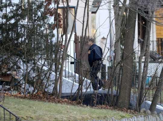 A Yonkers police officer walks toward a house on Buckingham Road in Yonkers, as they investigate a shooting overnight, Dec. 8, 2018.