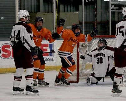 Dylan Mutkoski and Jake Cronin of Horace Greeley celebrate the team's second goal Friday on Scarsdale goalie Max Kushnick at the EJ Murray Skating Center in Yonkers. Greeley defeated Scarsdale, 2-1.