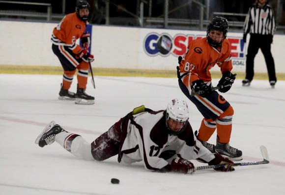 Arthur Mortreux of Scarsdale and Ben Cohen of Horace Greeley chase the puck Friday at the EJ Murray Skating Center in Yonkers. Greeley won, 2-1.