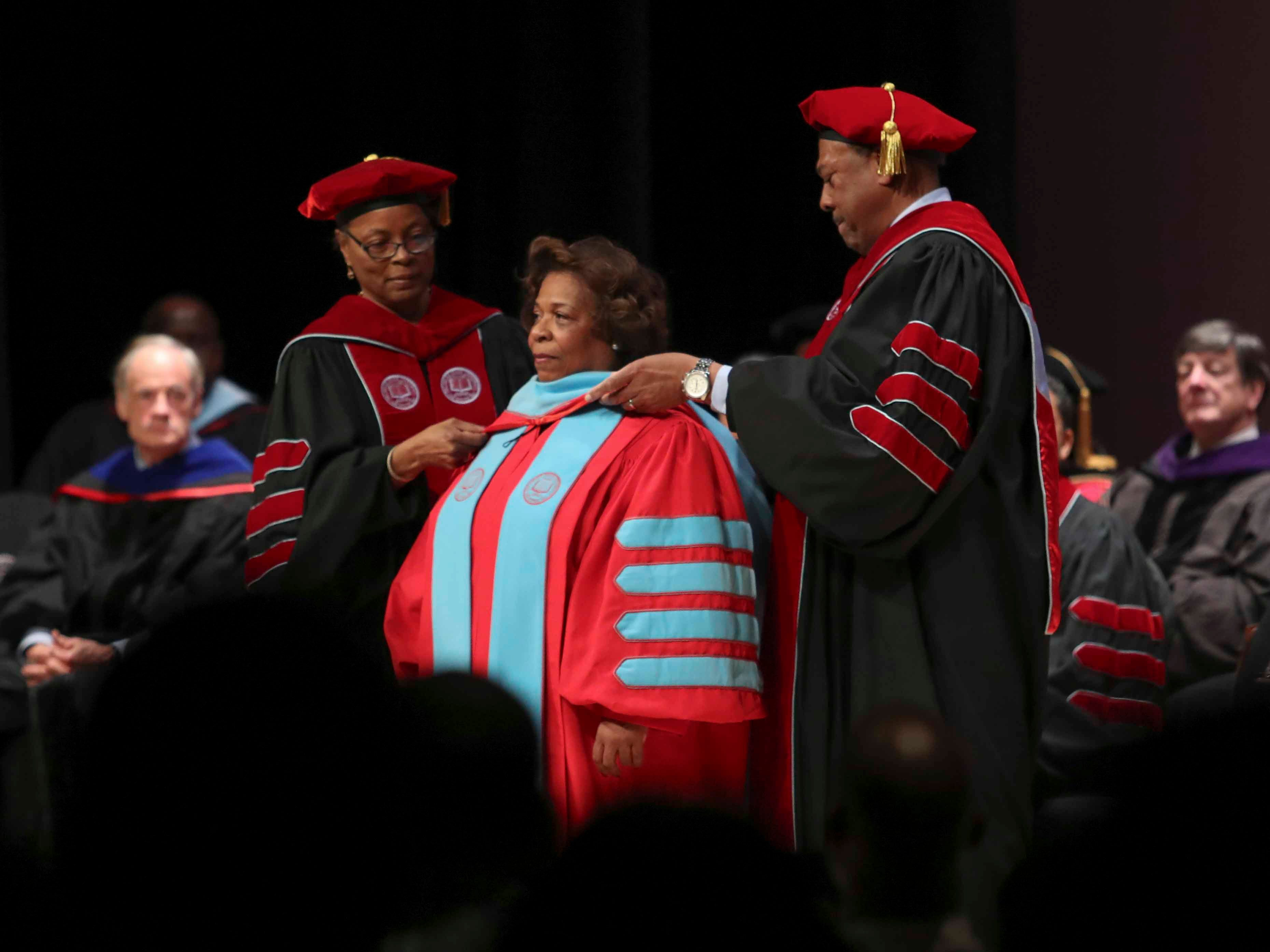 Wilma Mishoe receives the hood and gown of the presidency of Delaware State University by board of trustees members Debbie Harrington and John Ridgeway as she is formally conferred with the presidency of Delaware State University in an investiture ceremony Saturday at the Dover campus. Mishoe, a daughter of the university's 7th president, had been interim president since January before being named president in July. She is the university's 11th president and first woman president.