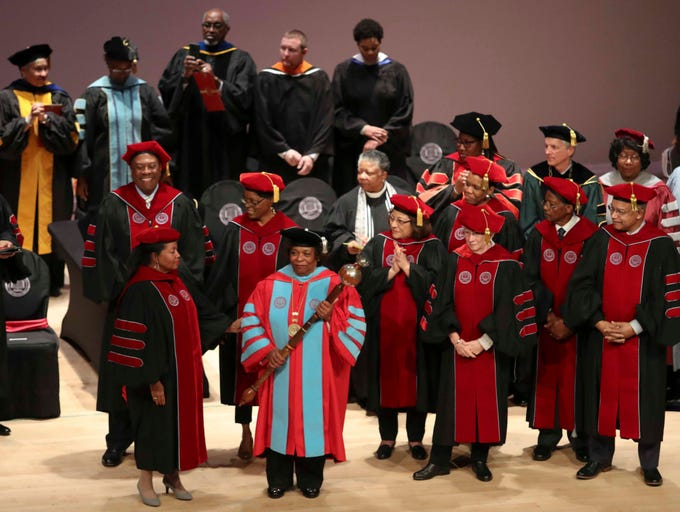 The board of trustees surround Wilma Mishoe as she is formally conferred with the presidency of Delaware State University in an investiture ceremony Saturday at the Dover campus. Mishoe, a daughter of the university's 7th president, had been interim president since January before being named president in July. She is the university's 11th president and first woman president.