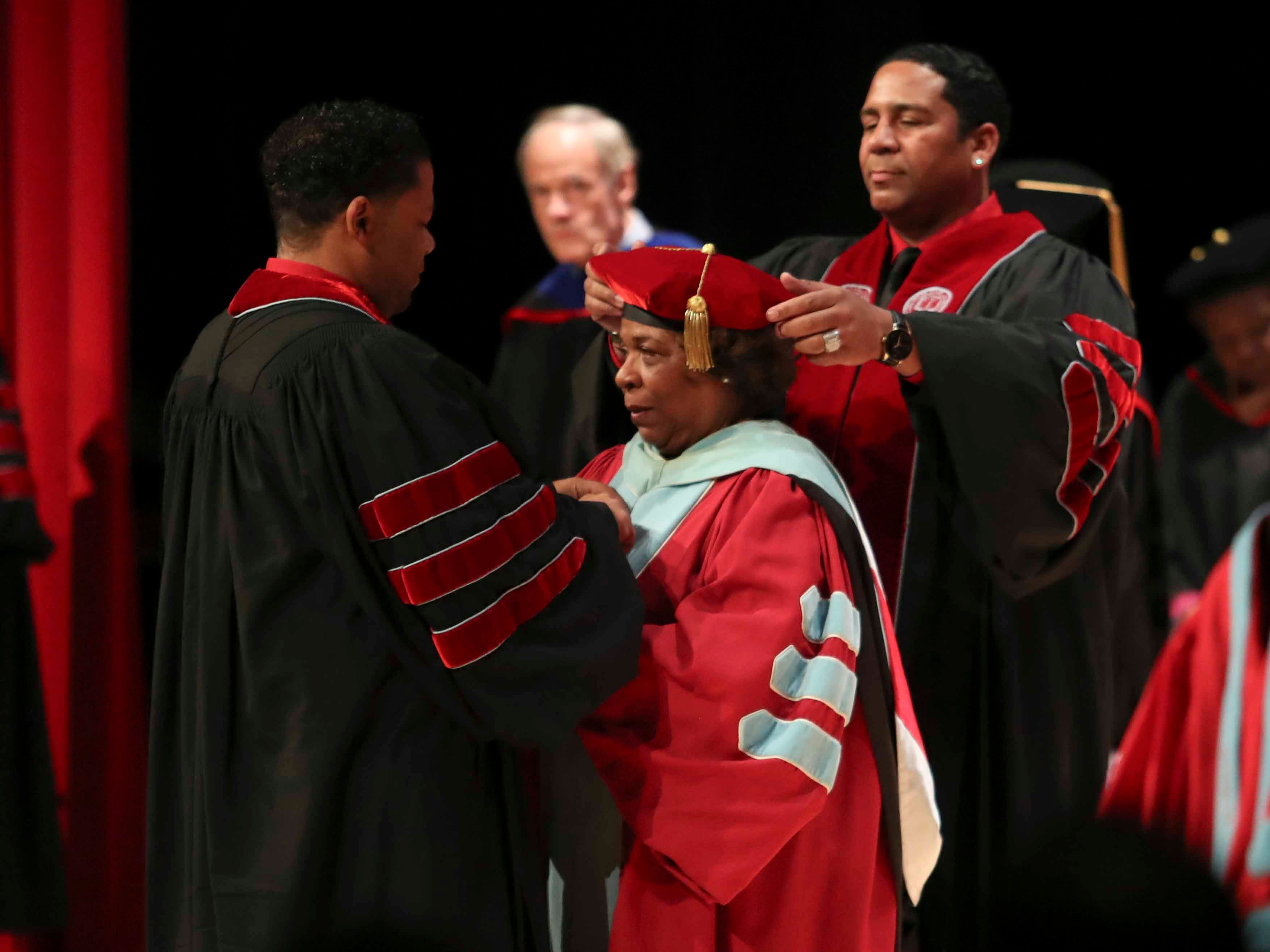 Wilma Mishoe's sons, Roy Sudler, Jr., and Travis Sudler, remove her academic regalia as she prepares to take on the president's hood and gown while being formally conferred with the presidency of Delaware State University in an investiture ceremony Saturday at the Dover campus. Mishoe, a daughter of the university's 7th president, had been interim president since January before being named president in July. She is the university's 11th president and first woman president.