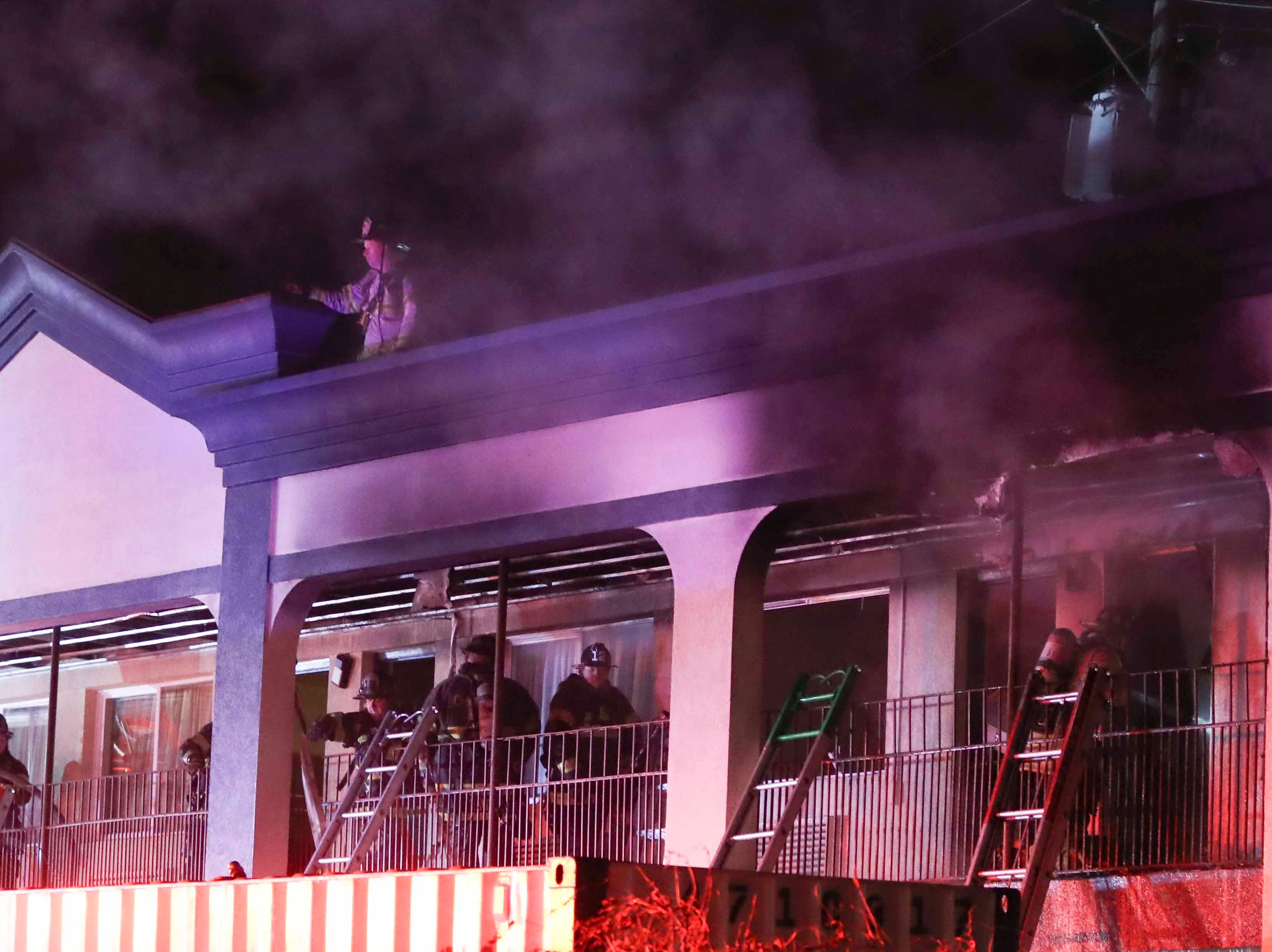 Firefighters work after extinguishing a two-alarm fire in the Super 8 Motel on Newark's Main Street late Friday. Firefighters, alerted to the blaze about 10:45 p.m. , found flames coming from the second floor of one end of the structure. There were no immediate reports of injuries.