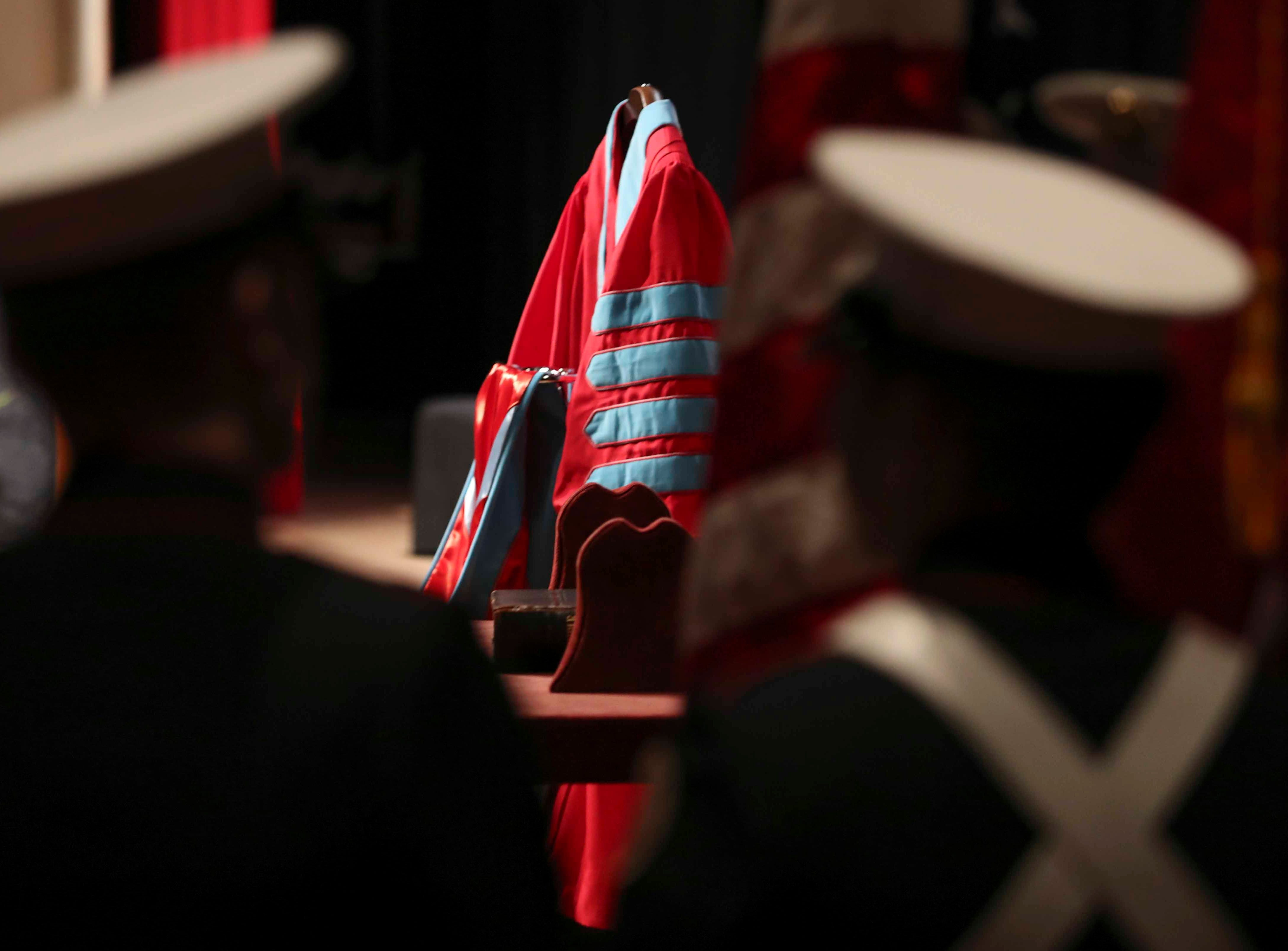 Members of the First State Military Academy color guard wait for the start of ceremonies as the academic regalia of Wilma Mishoe rests on the stage before her investiture ceremony Saturday at the Dover campus. Mishoe, a daughter of the university's 7th president, had been interim president since January before being named president in July. She is the university's 11th president and first woman president.