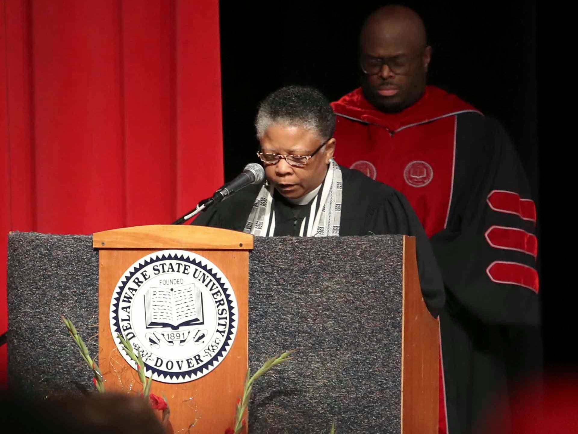 Rev. Rita Mishoe Paige delivers the invocation as her sister, Wilma Mishoe, is formally conferred with the presidency of Delaware State University in an investiture ceremony Saturday at the Dover campus. Mishoe, a daughter of the university's 7th president, had been interim president since January before being named president in July. She is the university's 11th president and first woman president.