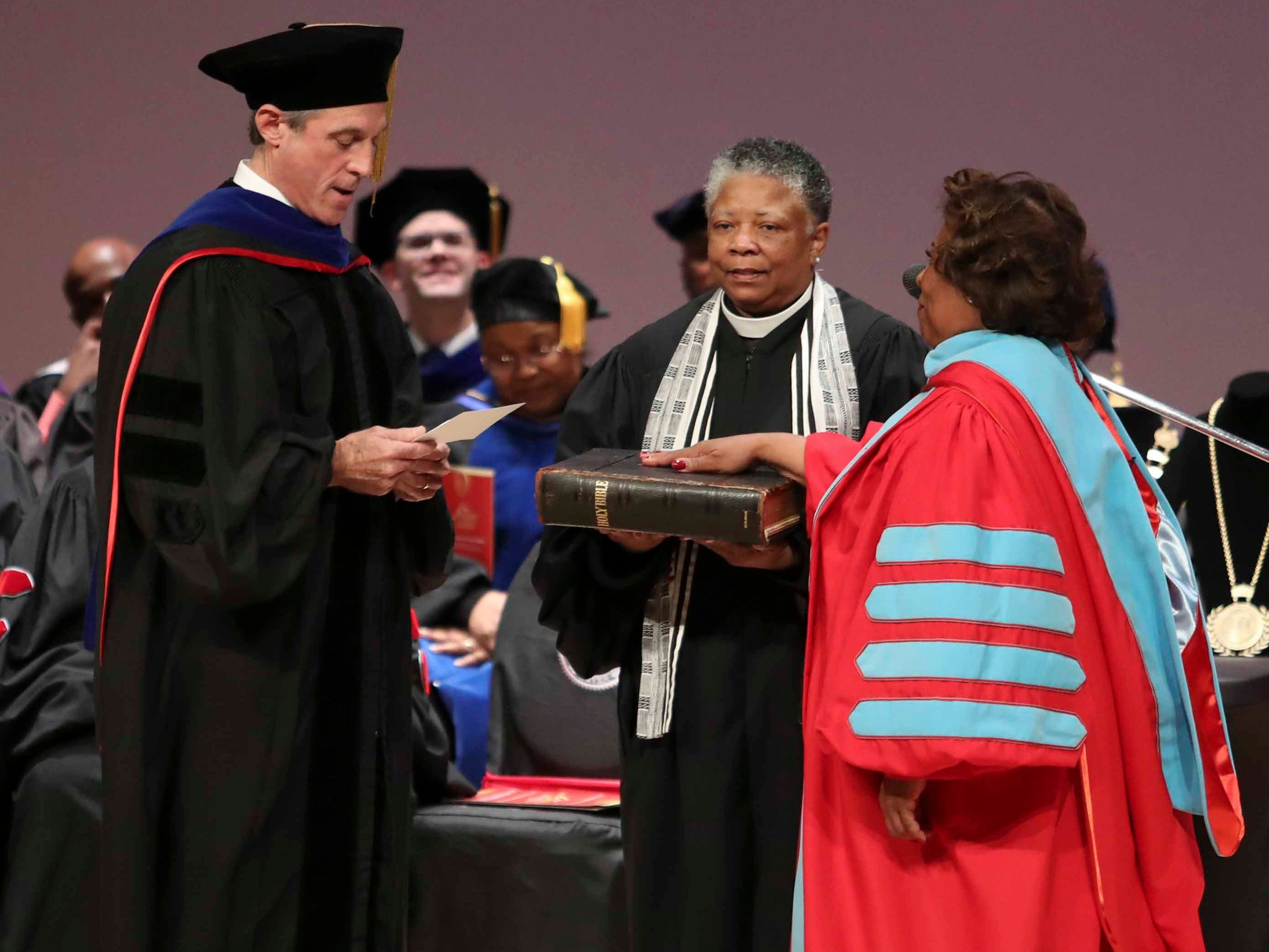 Wilma Mishoe is administered the oath of office from Gov. John Carney as her sister, Rev. Rita Mishoe Paige, holds a bible while Mishoe is formally conferred with the presidency of Delaware State University in an investiture ceremony Saturday at the Dover campus. Mishoe, a daughter of the university's 7th president, had been interim president since January before being named president in July. She is the university's 11th president and first woman president.