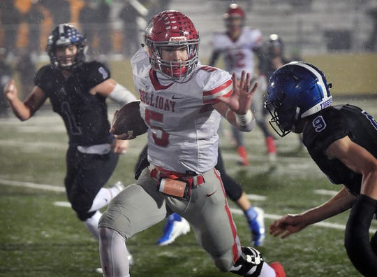 Holliday quarterback Jett Johnson (5) is challenged by Gunter's Grant McAfee (9) on a run in the second quarter of Friday night's game in Denison.