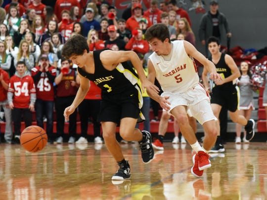 Tri-Valley's Ty Smith, left, and Sheridan's Costa Coconis chase a loose ball during the third quarter of their game on Friday night at Glen Hursey Gymnasium. Sheridan won the game, 65-46.