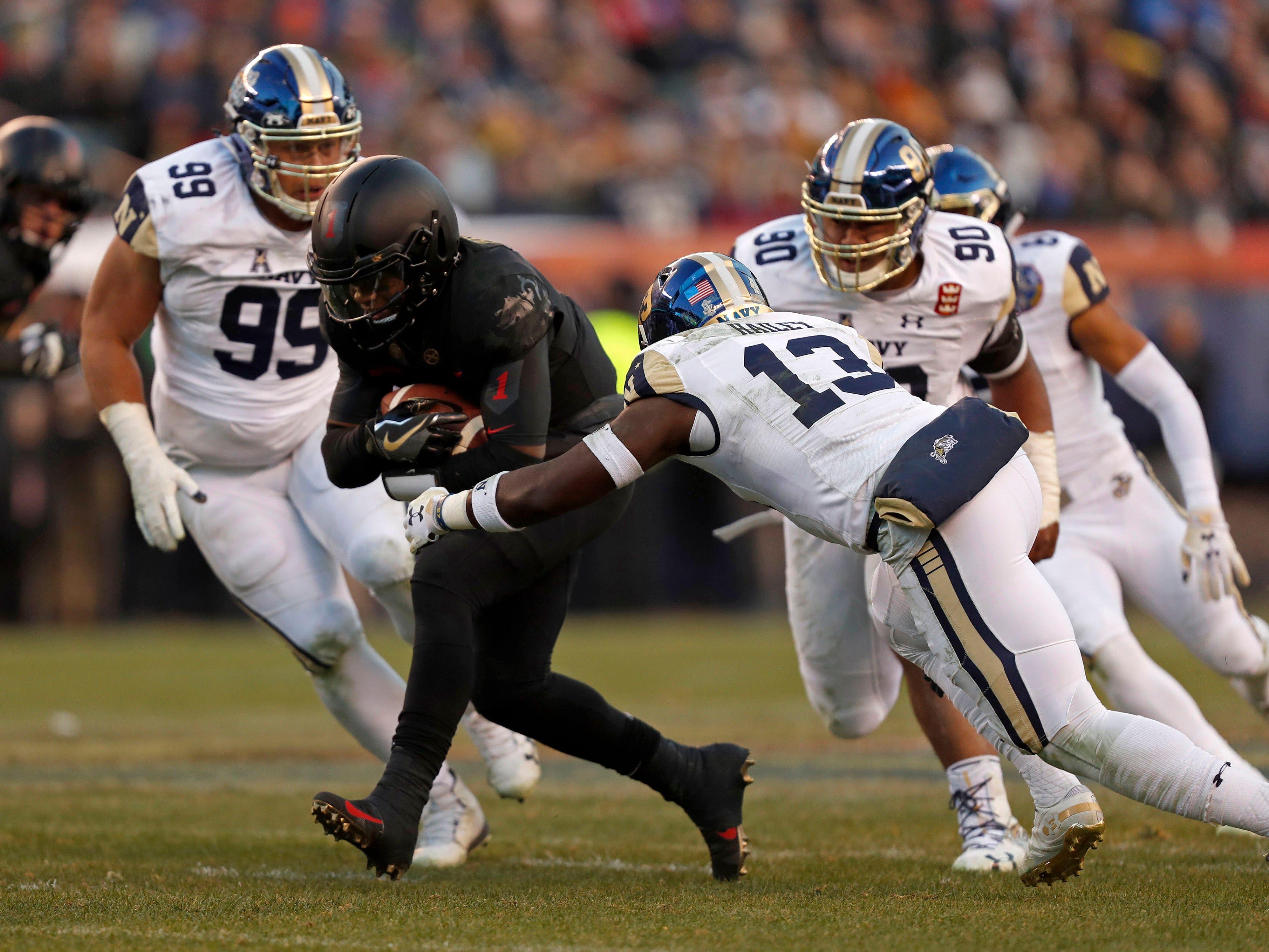 Army Black Knights quarterback Kelvin Hopkins Jr. runs the ball against Navy Midshipmen safety Juan Hailey during the first quarter.