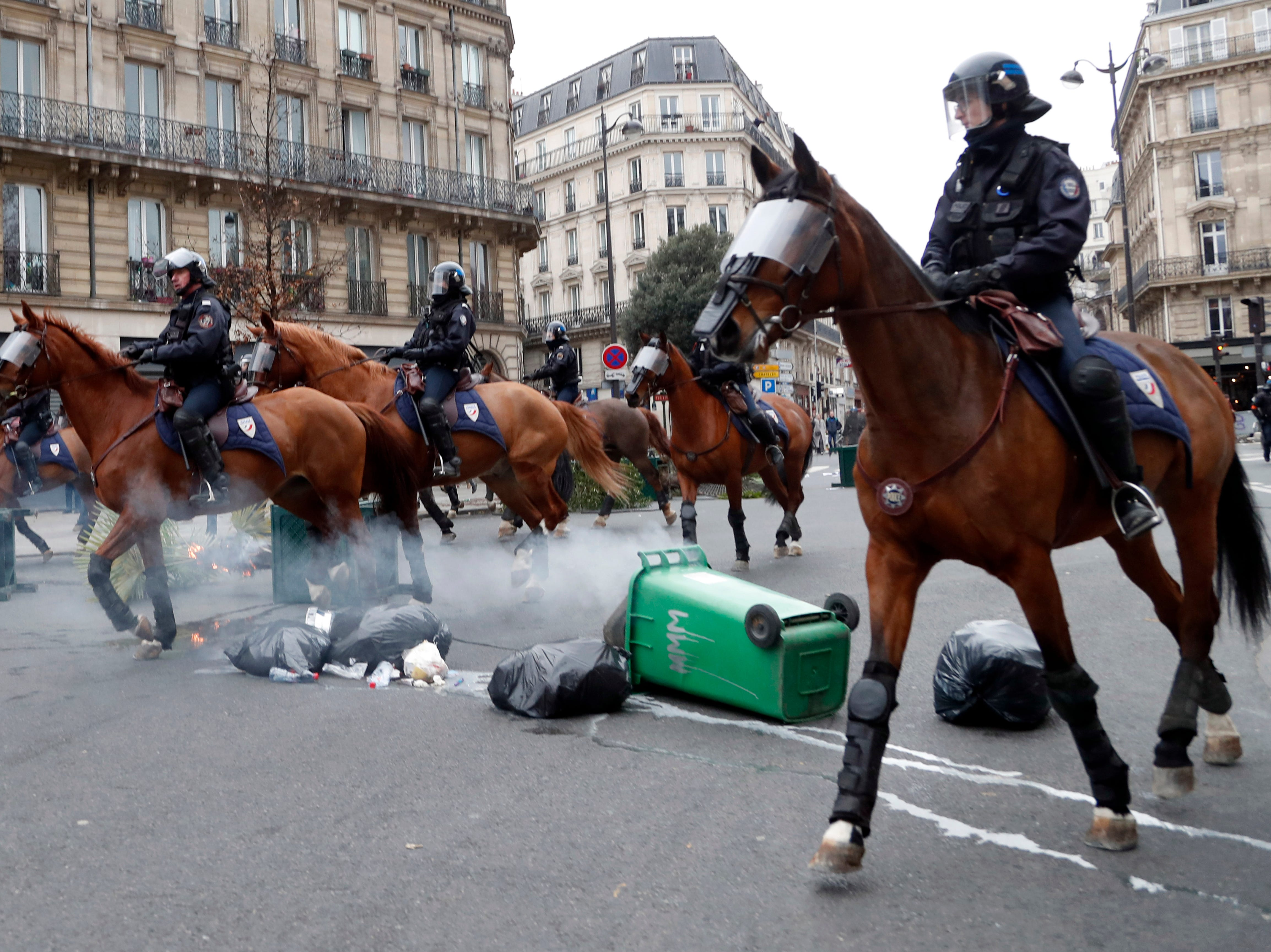Mounted Police officers on their horses take their positions during clashes with yellow-vested protesters, in Paris, France, Saturday, Dec. 8, 2018. Crowds of protesters angry at President Emmanuel Macron and France's high taxes tried to converge on the presidential palace Saturday, some scuffling with police firing tear gas, amid exceptional security measures aimed at preventing a repeat of last week's rioting.