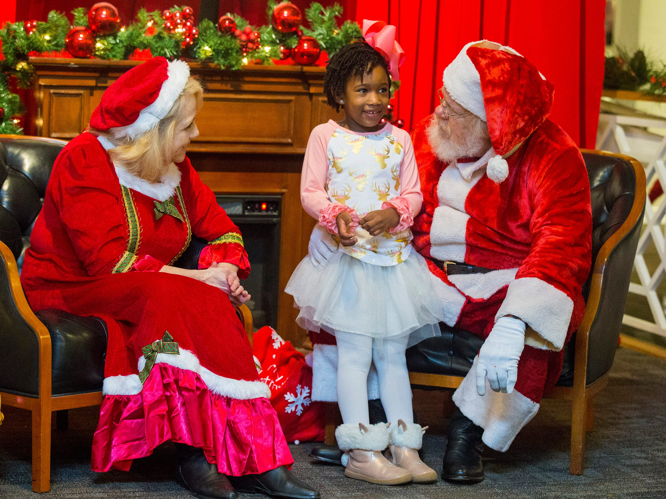 In this Saturday, Dec. 1, 2018 photo, Barbara Scott and Larry Bennett, playing Mrs. and Mr. Claus, talk with Cristilyn Jenkins about what she wants for Christmas during the Breakfast with Santa on at the Longview Museum of Fine Art in Longview, Texas.