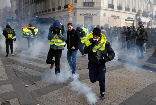 Demonstrators wearing yellow vests run away after police fired teargas during a protest in Paris, Saturday, Dec. 8, 2018. Prized Paris monuments and normally bustling shopping meccas locked down Saturday and tens of thousands of police took position around France, fearing worsening violence in a new round of anti-government protests.