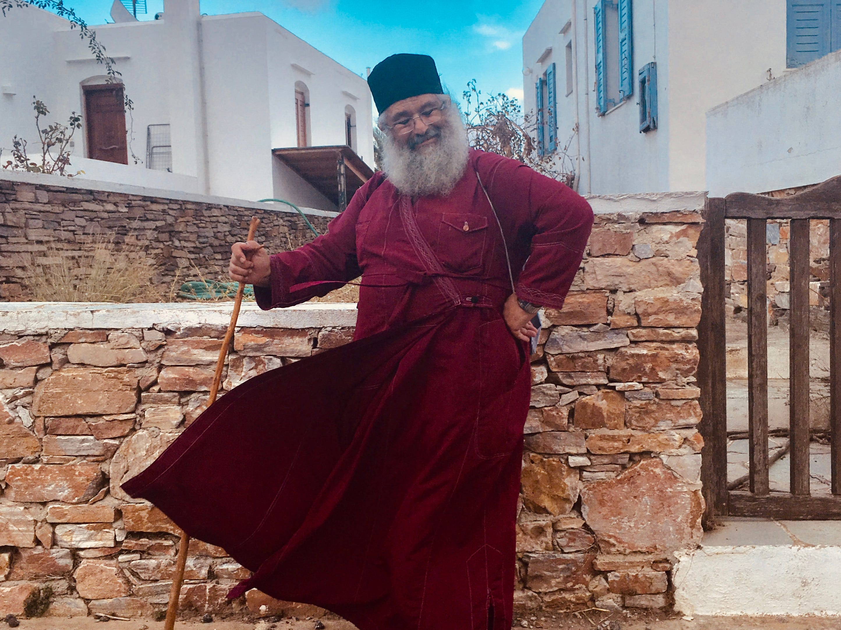 Greek islands with less tourism provide a greater chance for authentic experiences. Here a local priest poses for a photo.