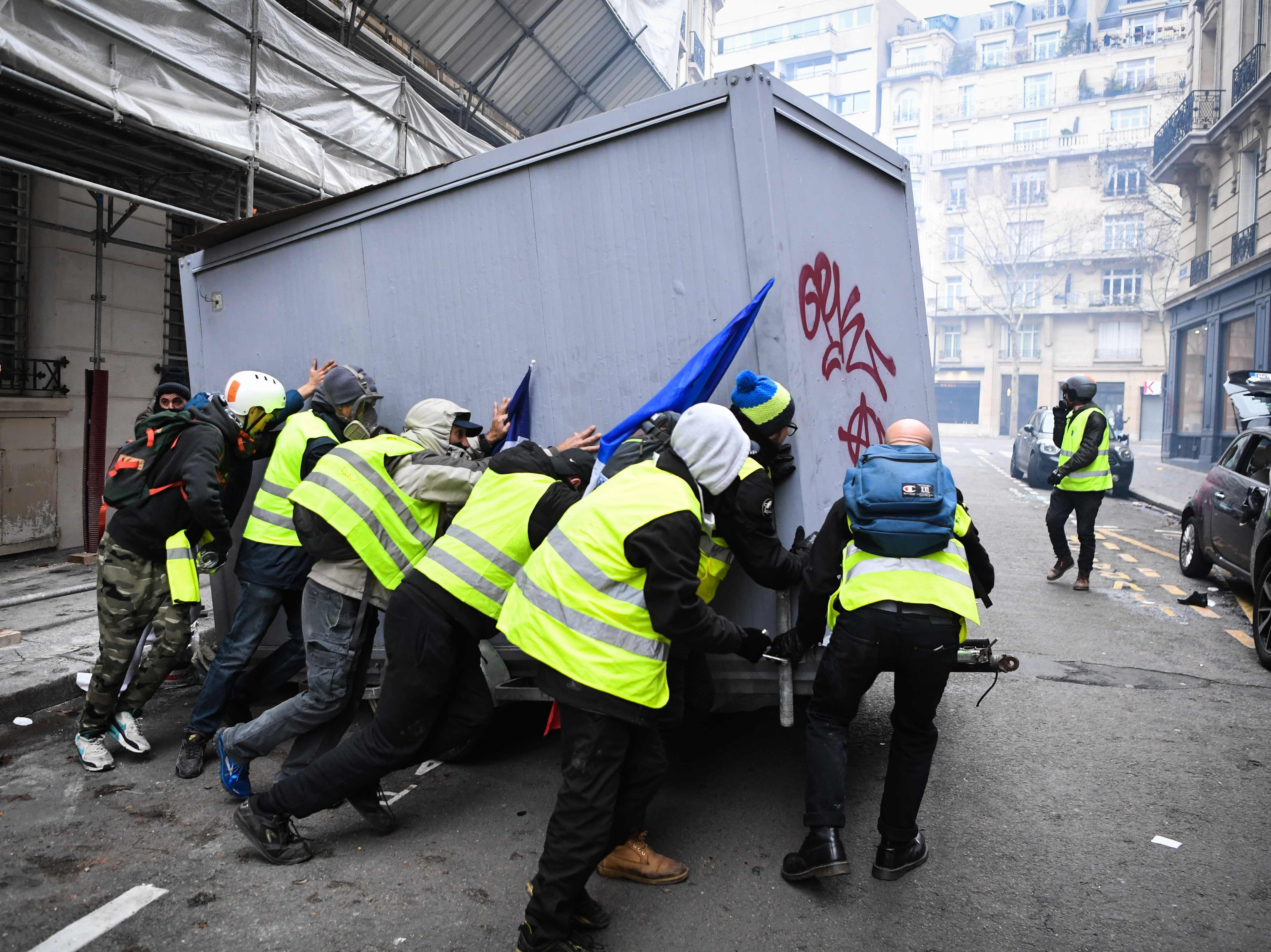 "Protestors move a container on December 8, 2018 in Paris, during a protest of ""yellow vests"" (gilets jaunes) against rising costs of living they blame on high taxes."