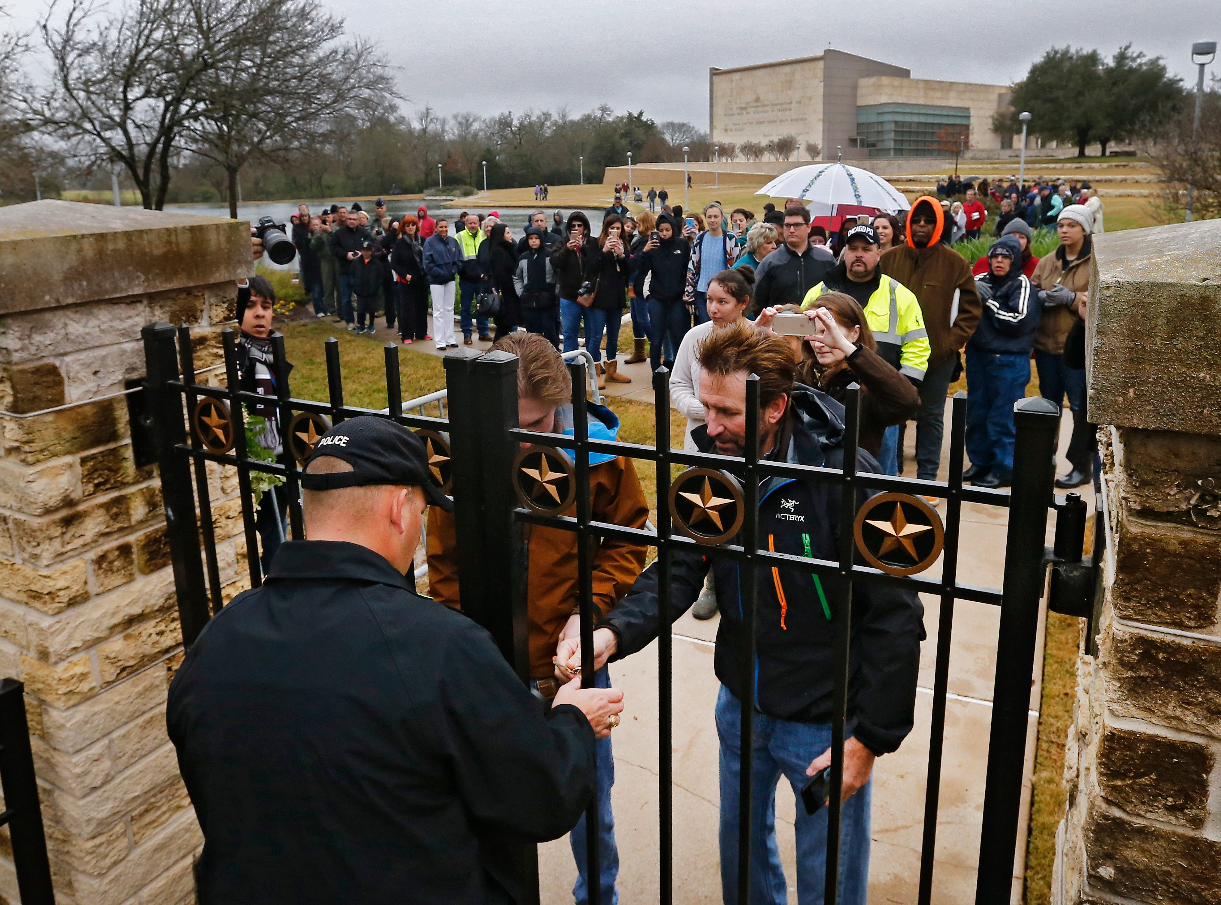 Security unlocks the gate for people waiting in line outside the gate to have a look at the gravesite of former US President George H.W. Bush, his wife Barbara Bush and their daughter Robin at the Presidential Library and Museum in College Station, Texas on Dec. 8, 2018.