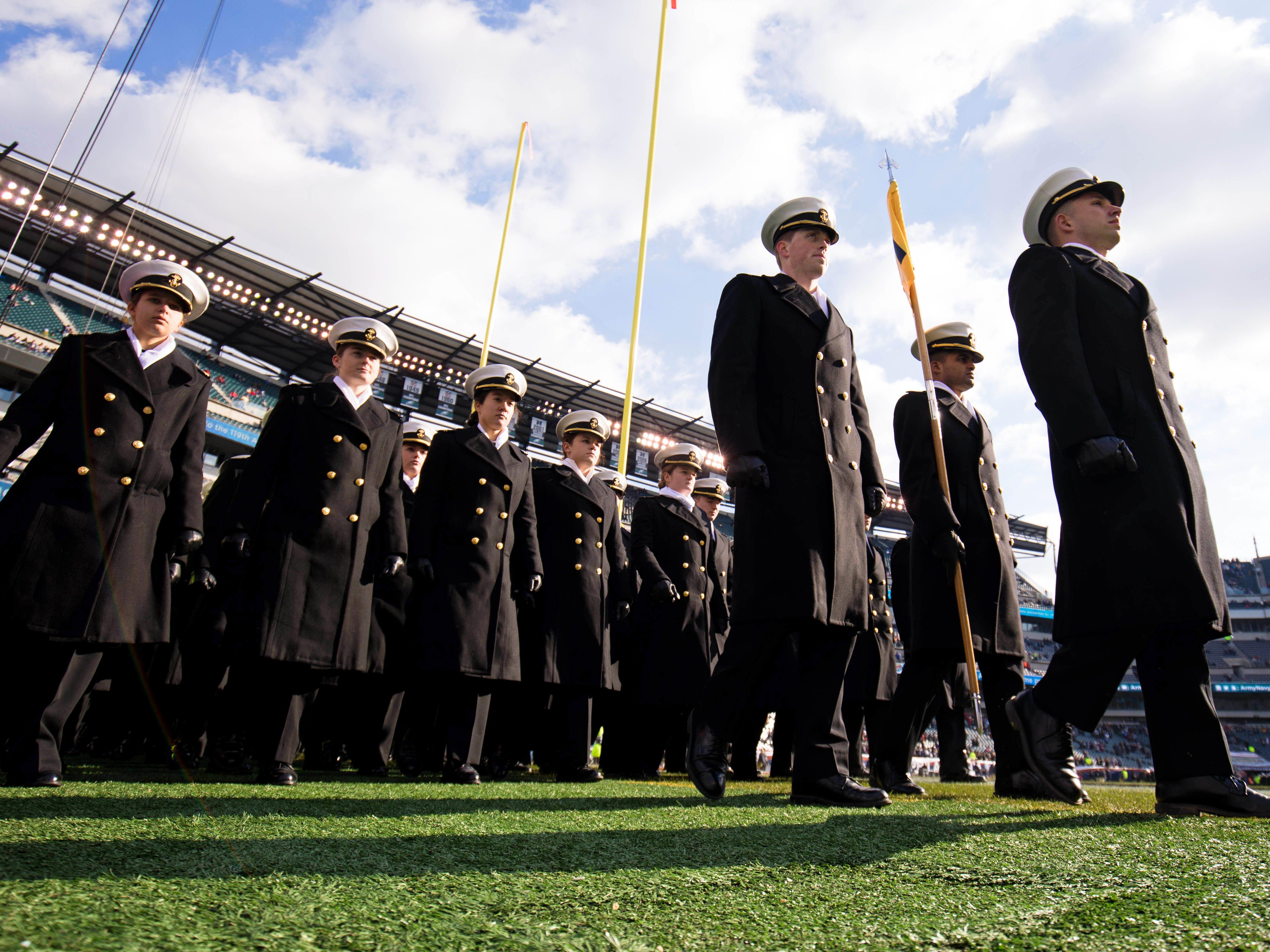 Navy Midshipmen march on the field.