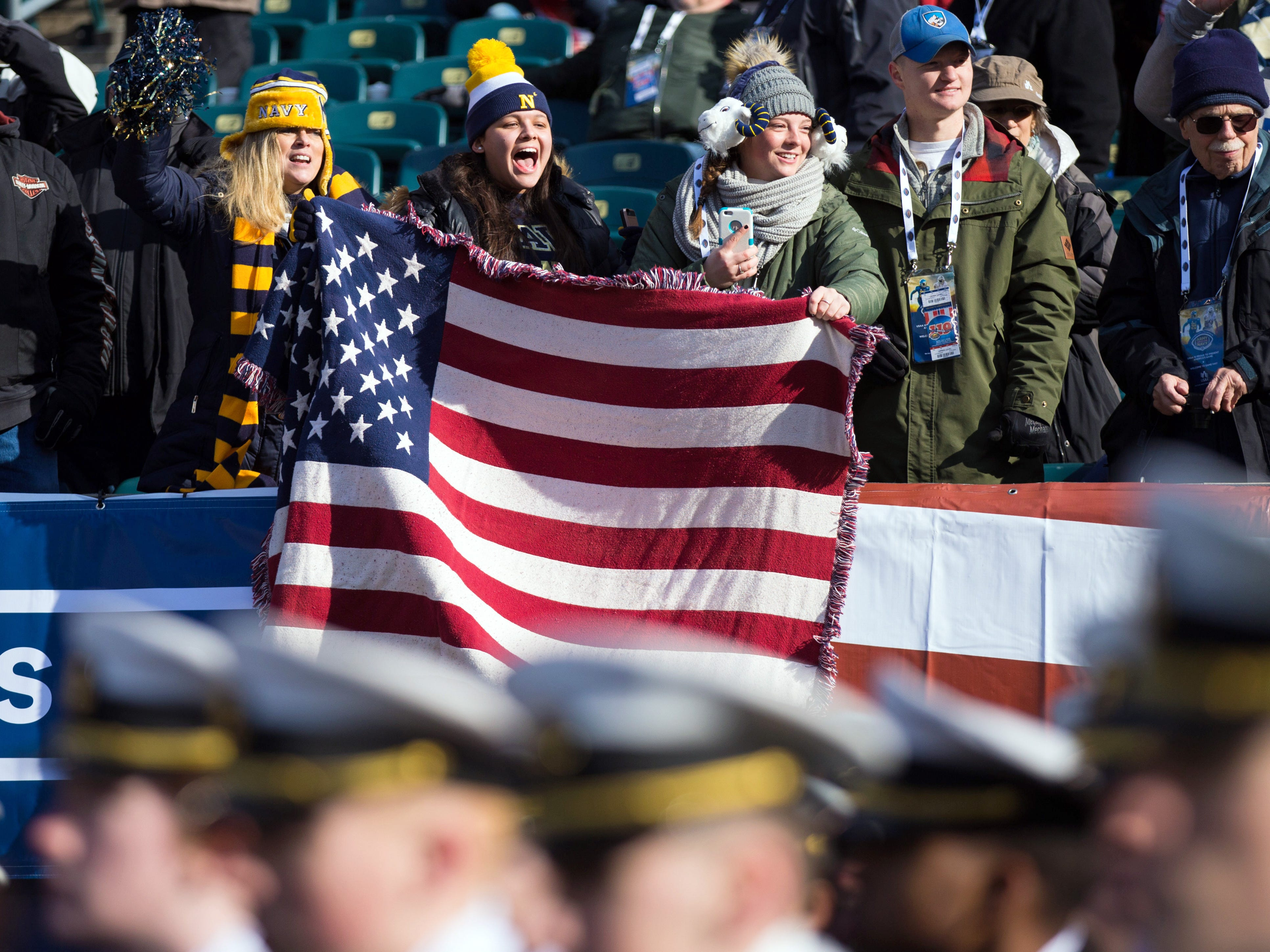 Navy fans cheer on as Navy Midshipmen march off the field.