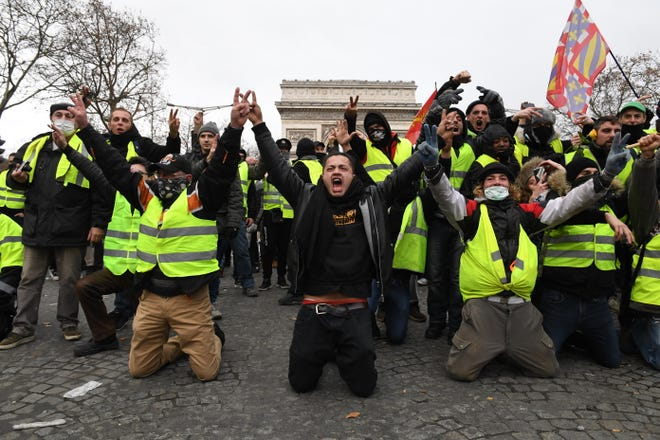 "Demonstrators kneel and gesture with victory signs as they take part in the demonstration of the yellow vests at the Arc de Triomphe on December 08, 2018 in Paris France. ''Yellow Vests' (""Gilet Jaunes"" or ""Vestes Jaunes"") is a protest movement without political affiliation which was inspired by opposition to a new fuel tax. After a month of protests, which have wrecked parts of Paris and other French cities, there are fears the movement has been infiltrated by""ultra-violent"" protesters. Today's protest has involved about 5,000 demonstrators so far, who have gathered in the Paris city centre, and police have made at least 211  arrests so far."
