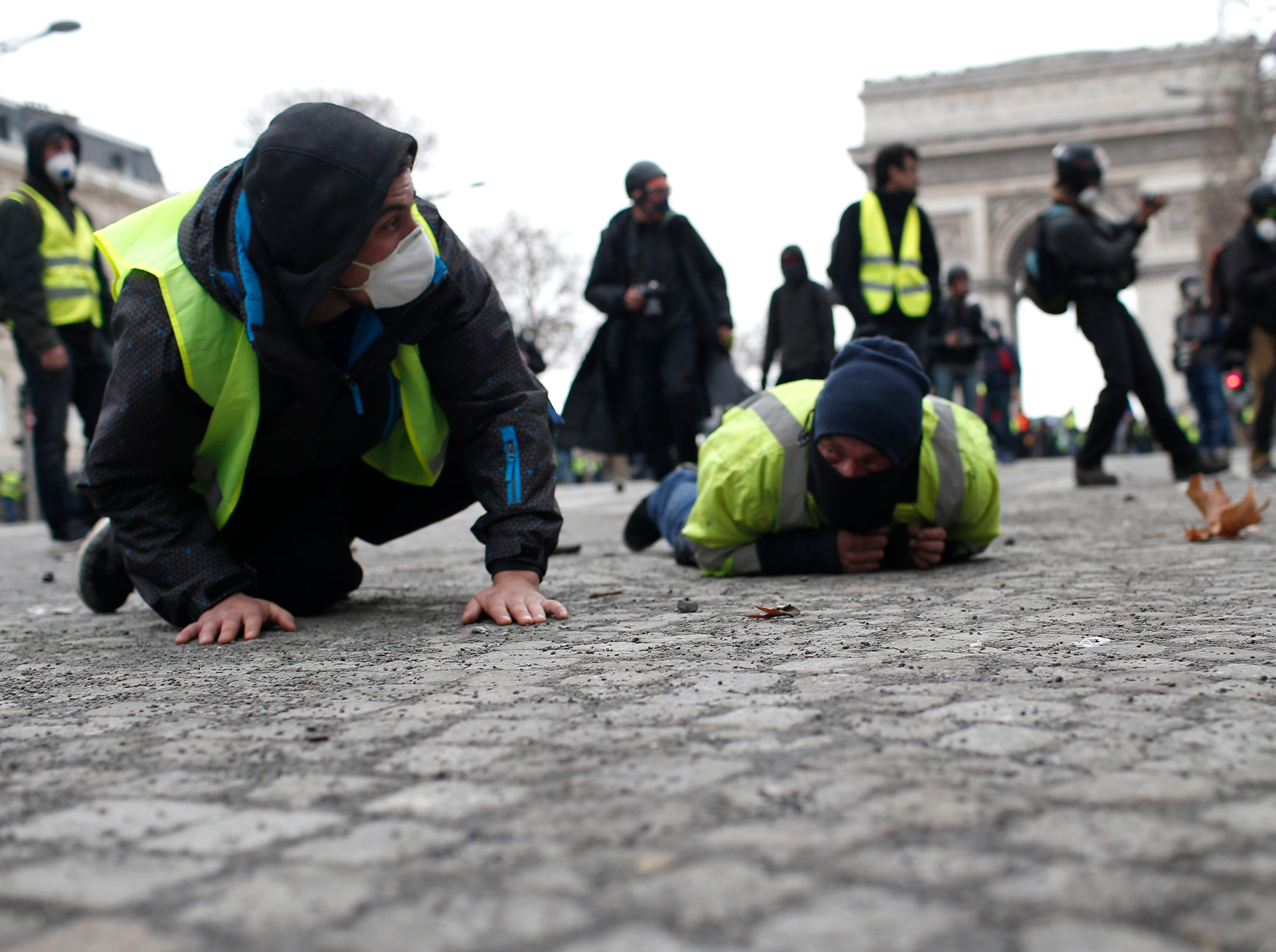 Demonstrators drop to the ground on the Champs-Elysees avenue during a protest Saturday, Dec. 8, 2018 in Paris. Crowds of yellow-vested protesters angry at President Emmanuel Macron and France's high taxes tried to converge on the presidential palace Saturday, some scuffling with police firing tear gas, amid exceptional security measures aimed at preventing a repeat of last week's rioting.