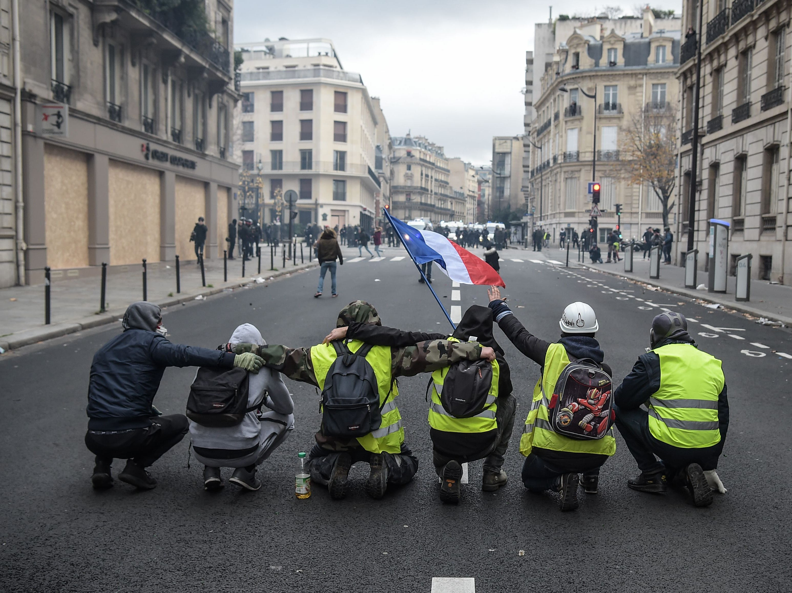 "Protestors kneel in a street near the Champs Elysees avenue in Paris on Dec. 8, 2018 during a protest of ""yellow vests"" (gilets jaunes) against rising costs of living they blame on high taxes."