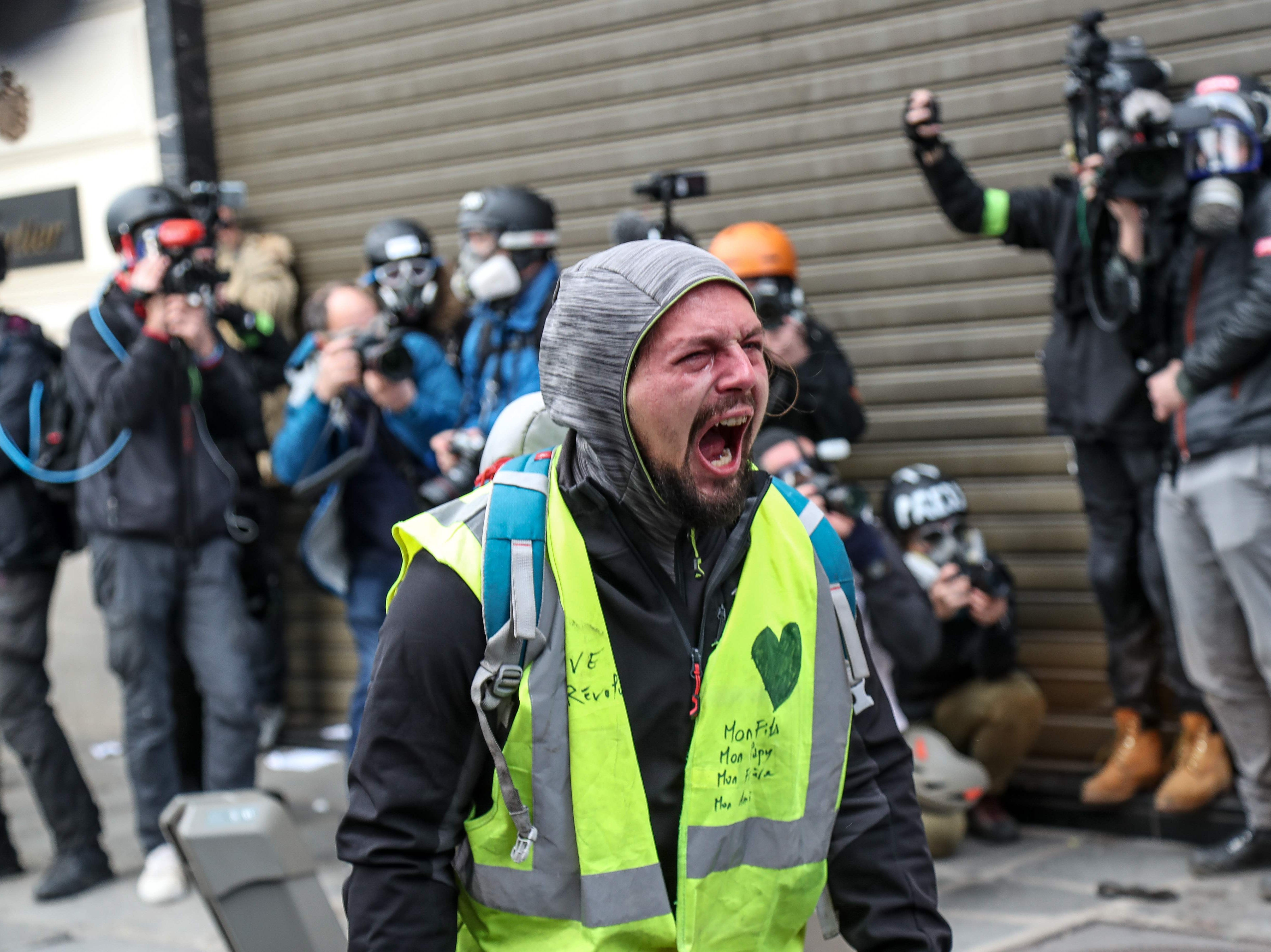 "A ""Yellow vest"" (gilet jaune) demonstrator faces a riot police near the Champs Elysees avenue in Paris on Dec. 8, 2018 during a mobilisation against rising costs of living they blame on high taxes."