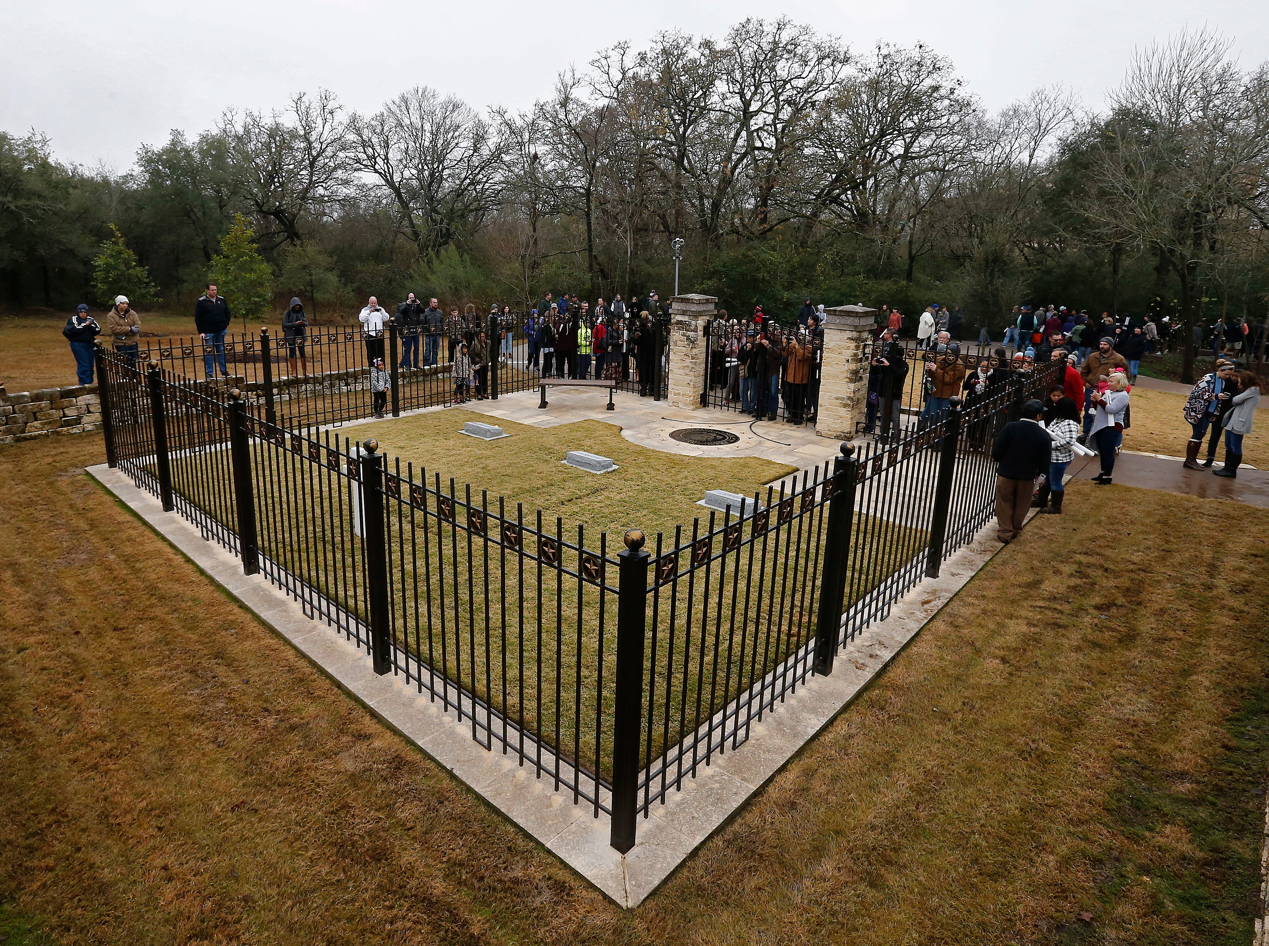 Visitors take pictures and look at the gravesite of former US President George H.W. Bush, center, his wife Barbara Bush, left, and their daughter Robin at the Presidential Library and Museum in College Station, Texas on Dec. 8, 2018. Bush died at the age of 94 on Nov. 30, 2018 at his home in Texas. George H.W. Bush was the 41st President of the United States (1989-1993).