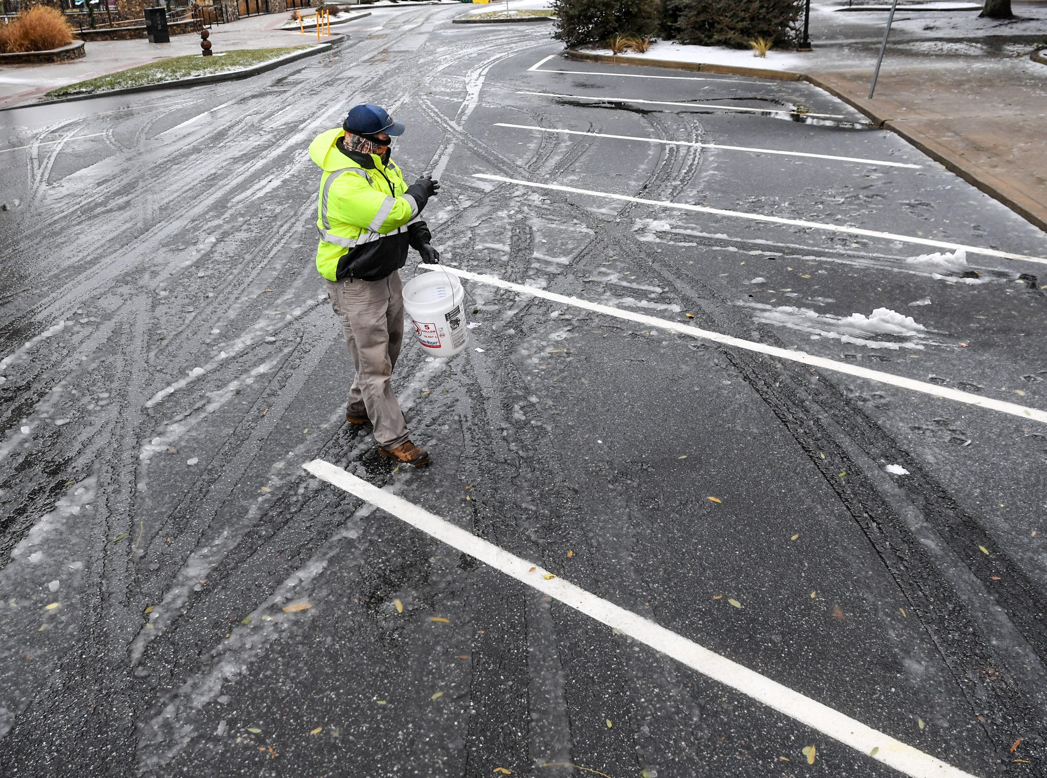 Collin Smith of the Anderson County Facilities tosses ice melt on parking area along West Whitner Street with a mix of snow and sleet Sunday morning, December 9, 2018.