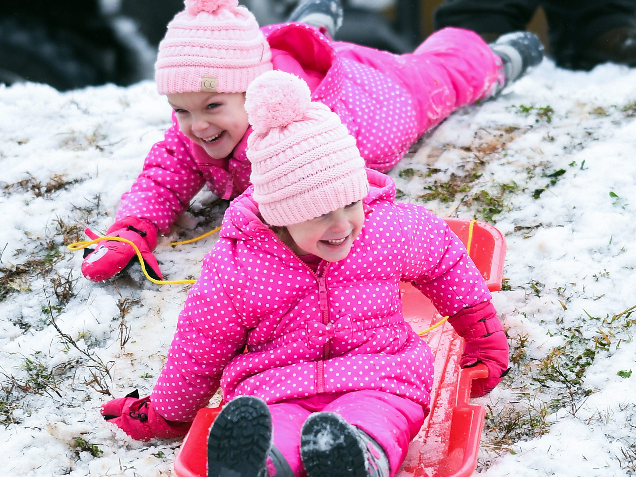 Twins Britt, front, and Addi Clinkscales sled down a hill in Belton after a layer of sleet fell early Sunday December 9, 2018.