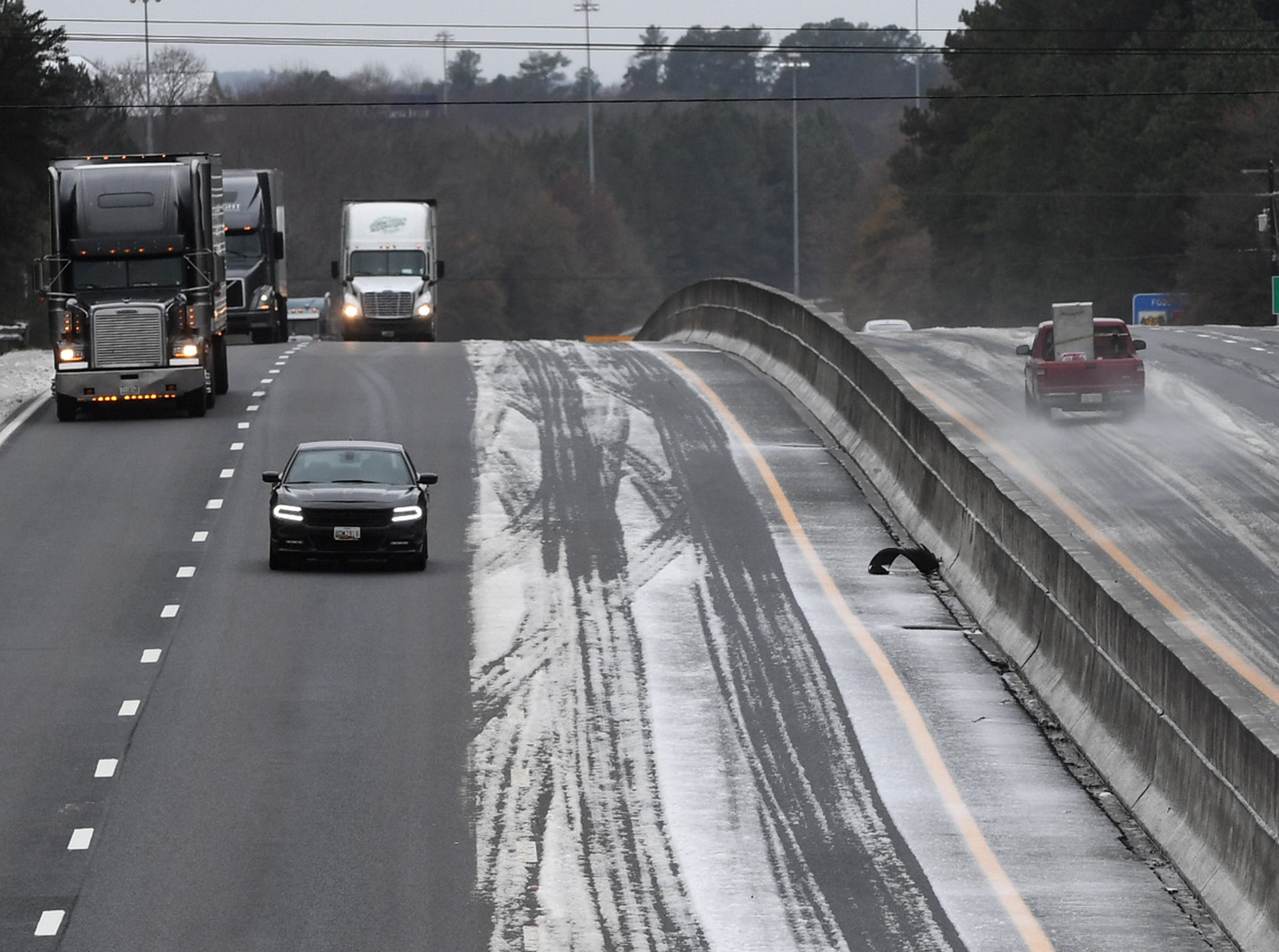 Cars drive through a mix of snow and sleet on I-85 near Highway 178 in Anderson County Sunday, December 9, 2018.
