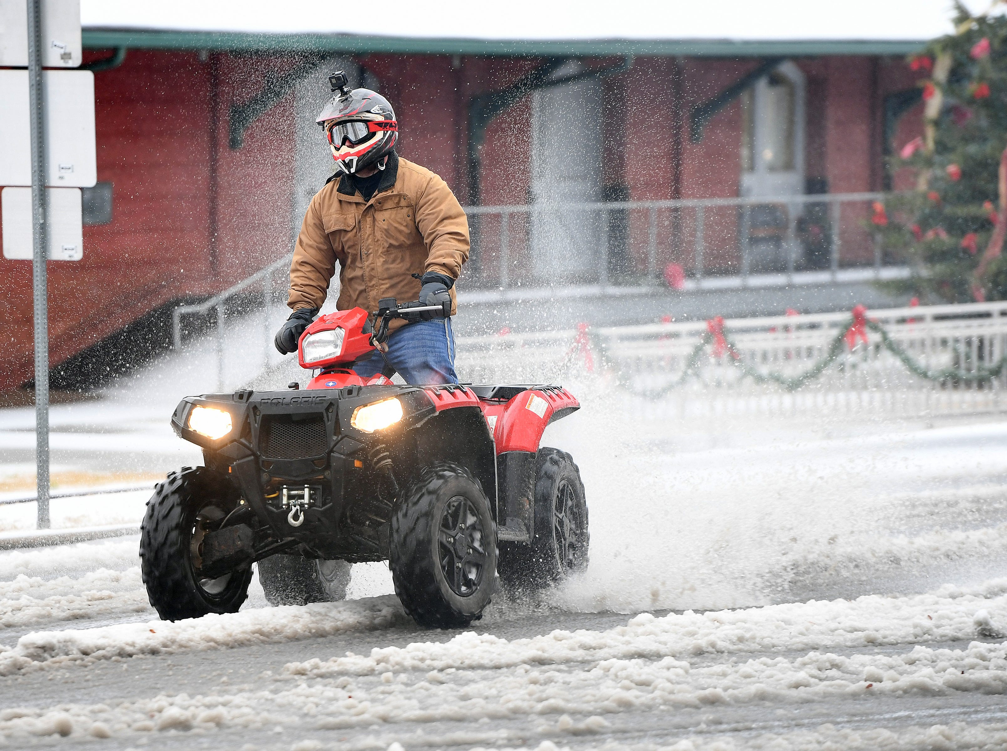 A four wheeler is driven on Main Street in downtown Belton after a layer of sleet fell early Sunday December 9, 2018.