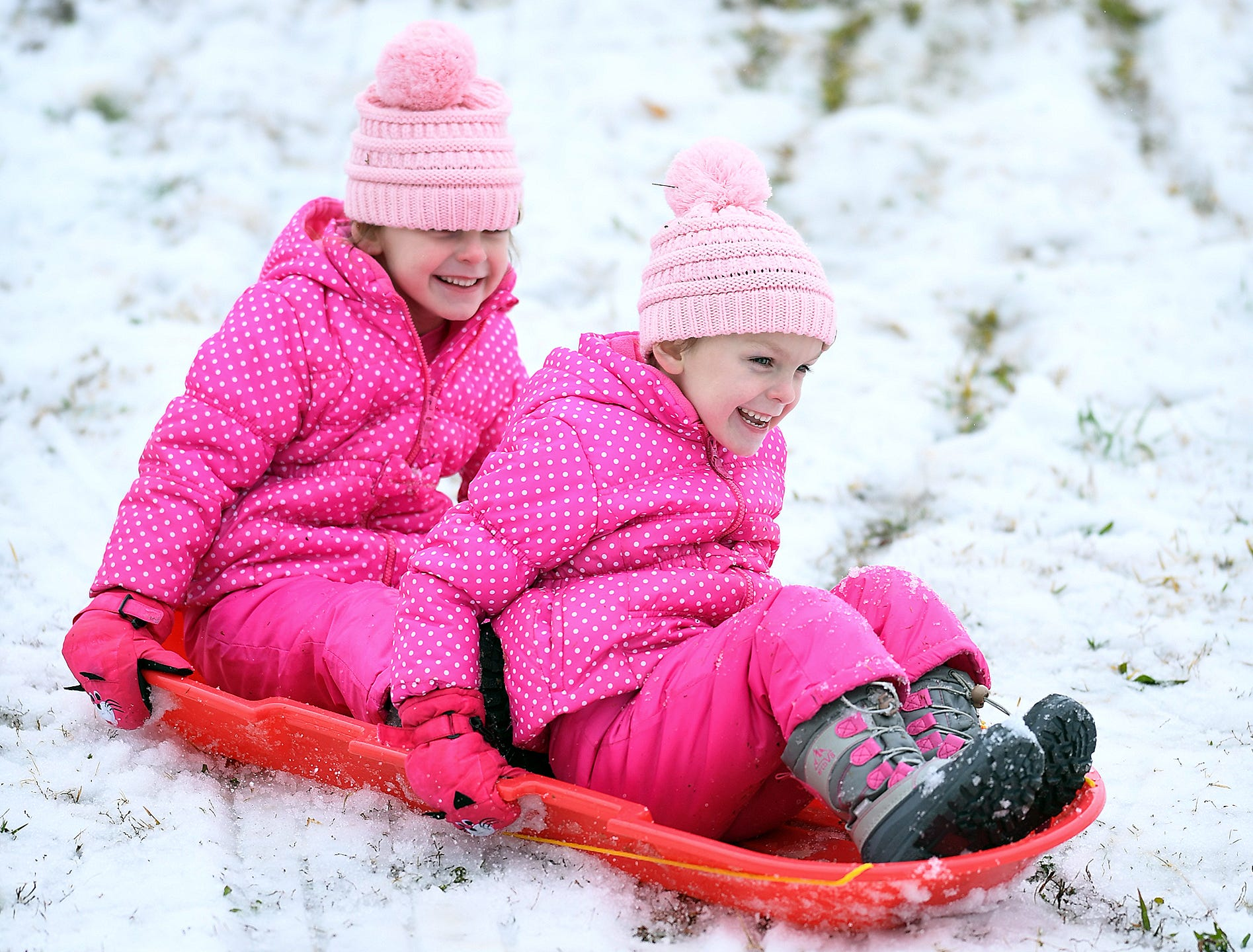 Twins Addi, front, and Britt Clinkscales sled down a hill in Belton after a layer of sleet fell early Sunday December 9, 2018.