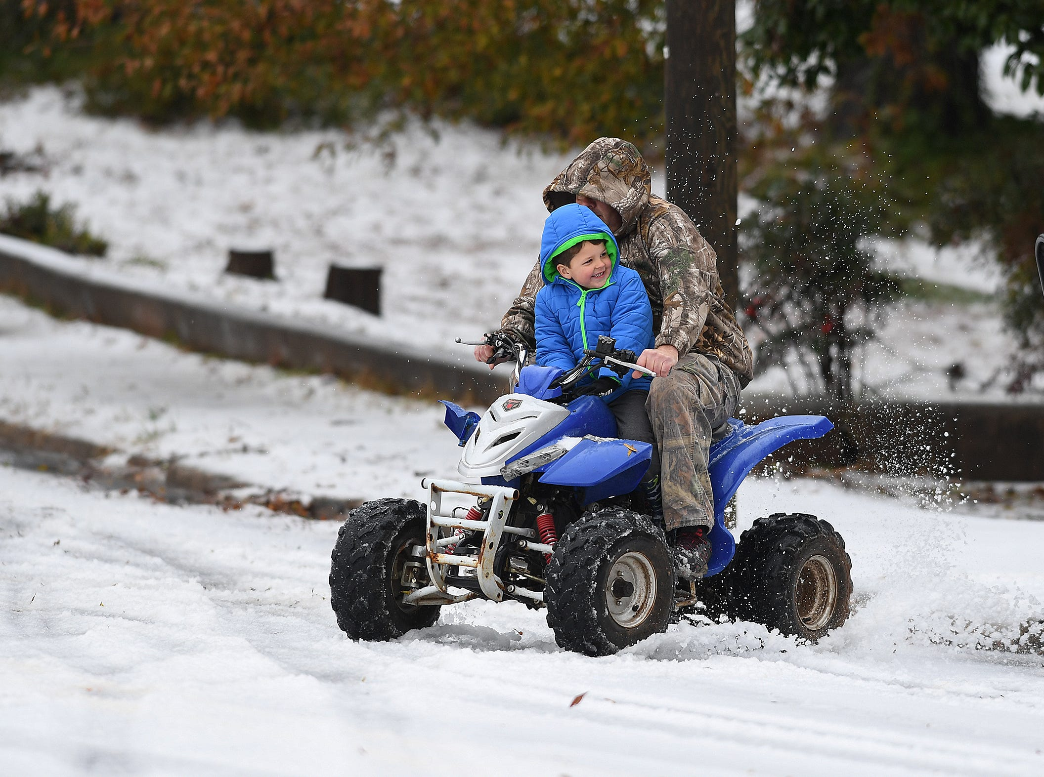 David Barbara rides his son Mason on a four wheeler in Belton after a layer of sleet fell early Sunday December 9, 2018.