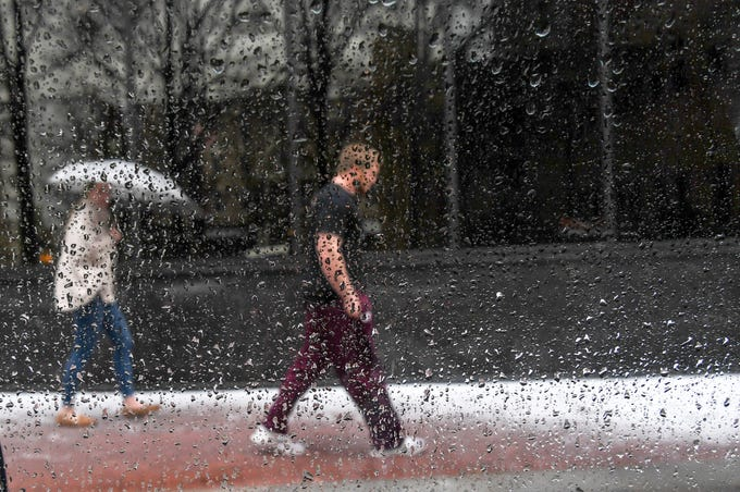 Sam and Lauren Rogers of Richmond, Va., visiting Anderson, walk through a mix of snow and sleet Sunday morning, December 9, 2018.