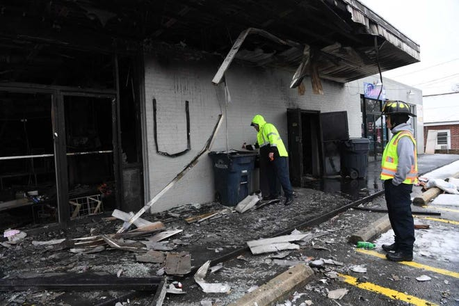 Anderson city firefighters inspect the damage after Saturday night's fire at the  Kezo Quick Stop convenience store on East Whitner Street.